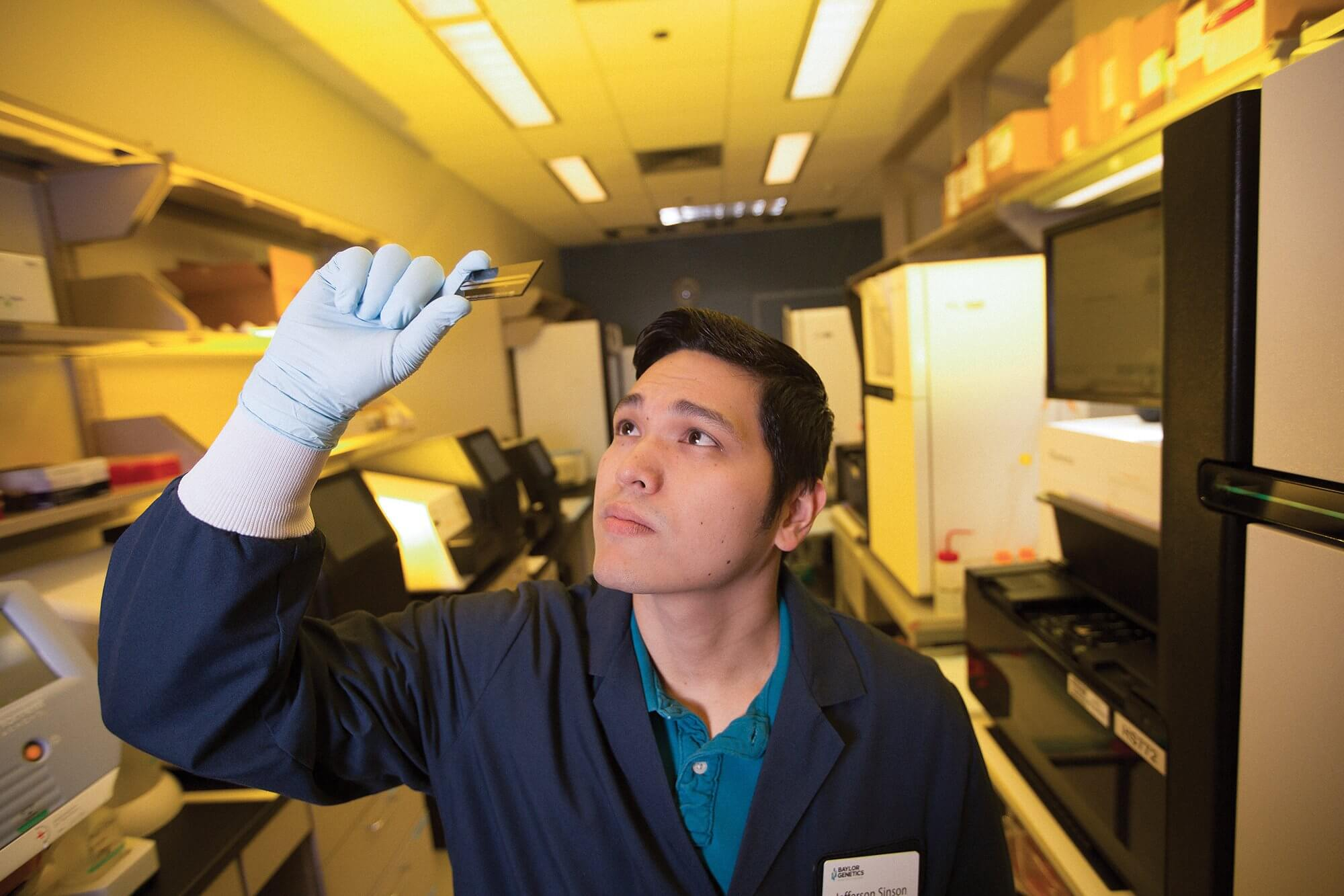 Jefferson Sinson, a research and development scientist at Baylor Genetics who worked on the development of the PreSeek test, holds up a slide containing cell-free DNA.