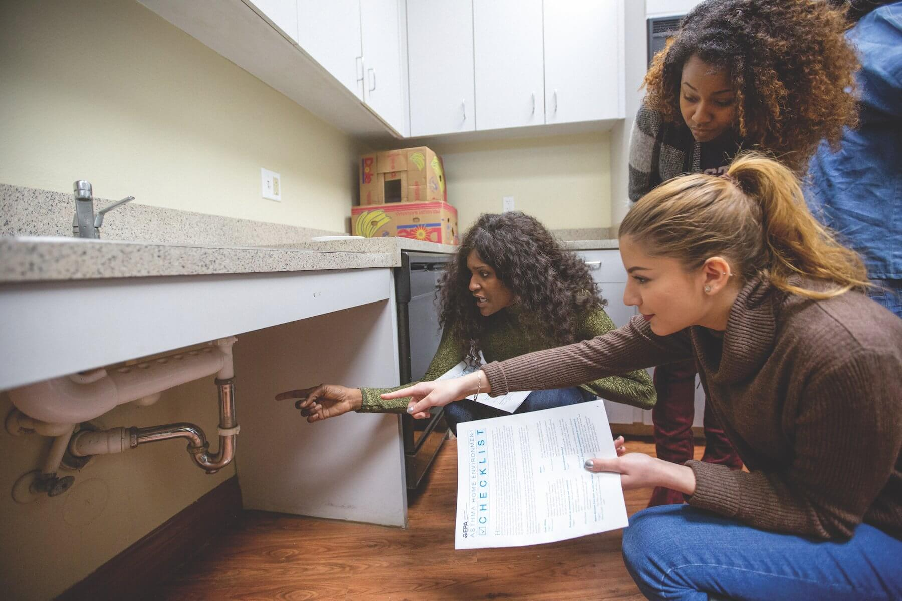 Sylvia Guilliam, left, and Nour Haikal, lower right, practice looking for mold in the kitchen of the Cuney Homes' recreation center.