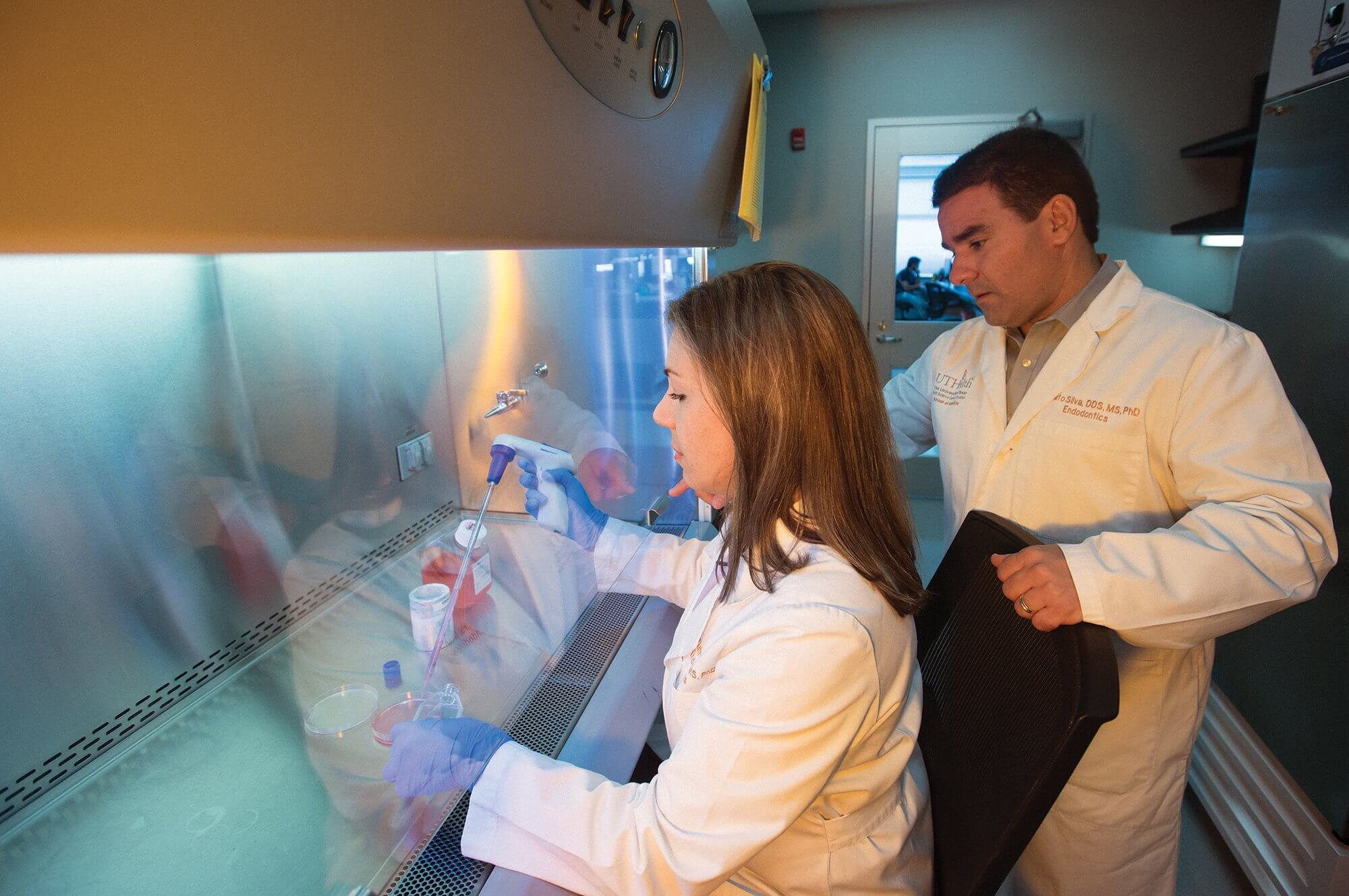 Ariadne Letra, D.D.S., Ph.D., director of research in the department of endodontics at UTHealth's School of Dentistry, and Renato Silva, D.D.S., Ph.D., associate professor and chair of the department of endodontics at UTHealth, demonstrate how their team analyzes samples.