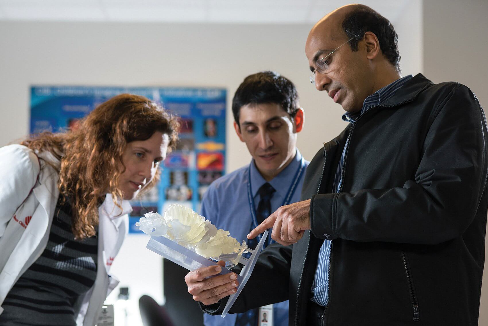 Rajesh Krishnamurthy, M.D., right, examines a 3-D printed model from a pair of conjoined twins. His team studied the model during surgical planning to get a more accurate understanding of the physiological structures and relationship of the organs. (Credit: Allen Kramer/Texas Children's Hospital)