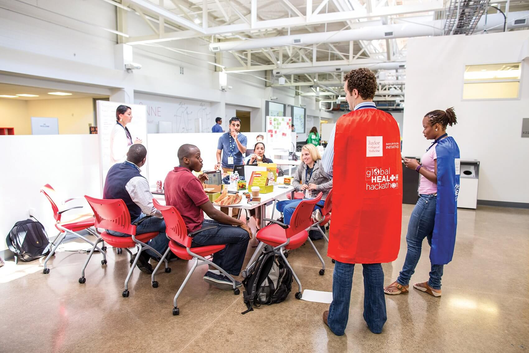 Mentor Seth Cochran (red cape) advises hackers on their pitch.