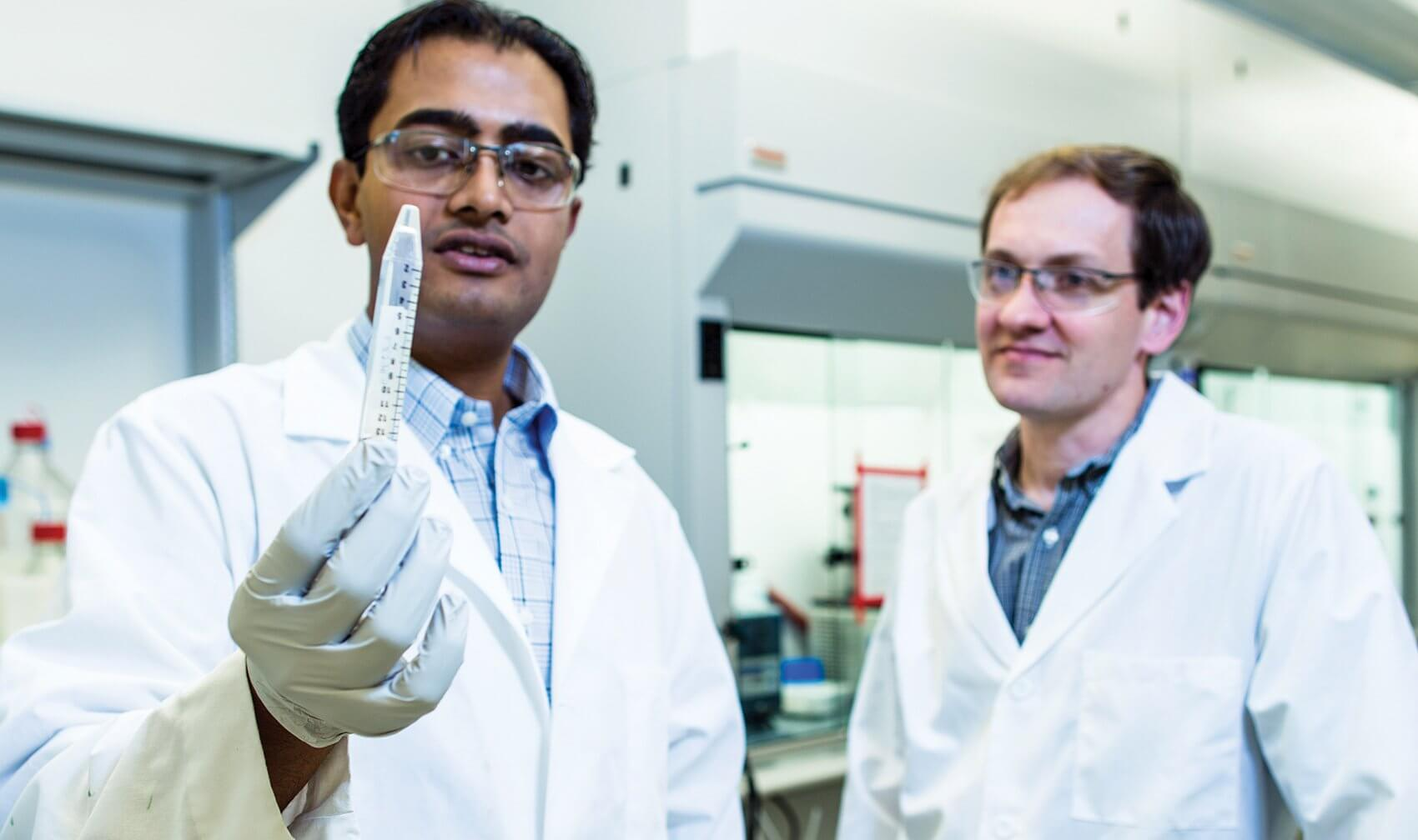 Vivek Kumar, Ph.D. and Jeff Hartgerink, Ph.D., display a vial of hydrogel they developed to stop bleeding in surgical patients.
