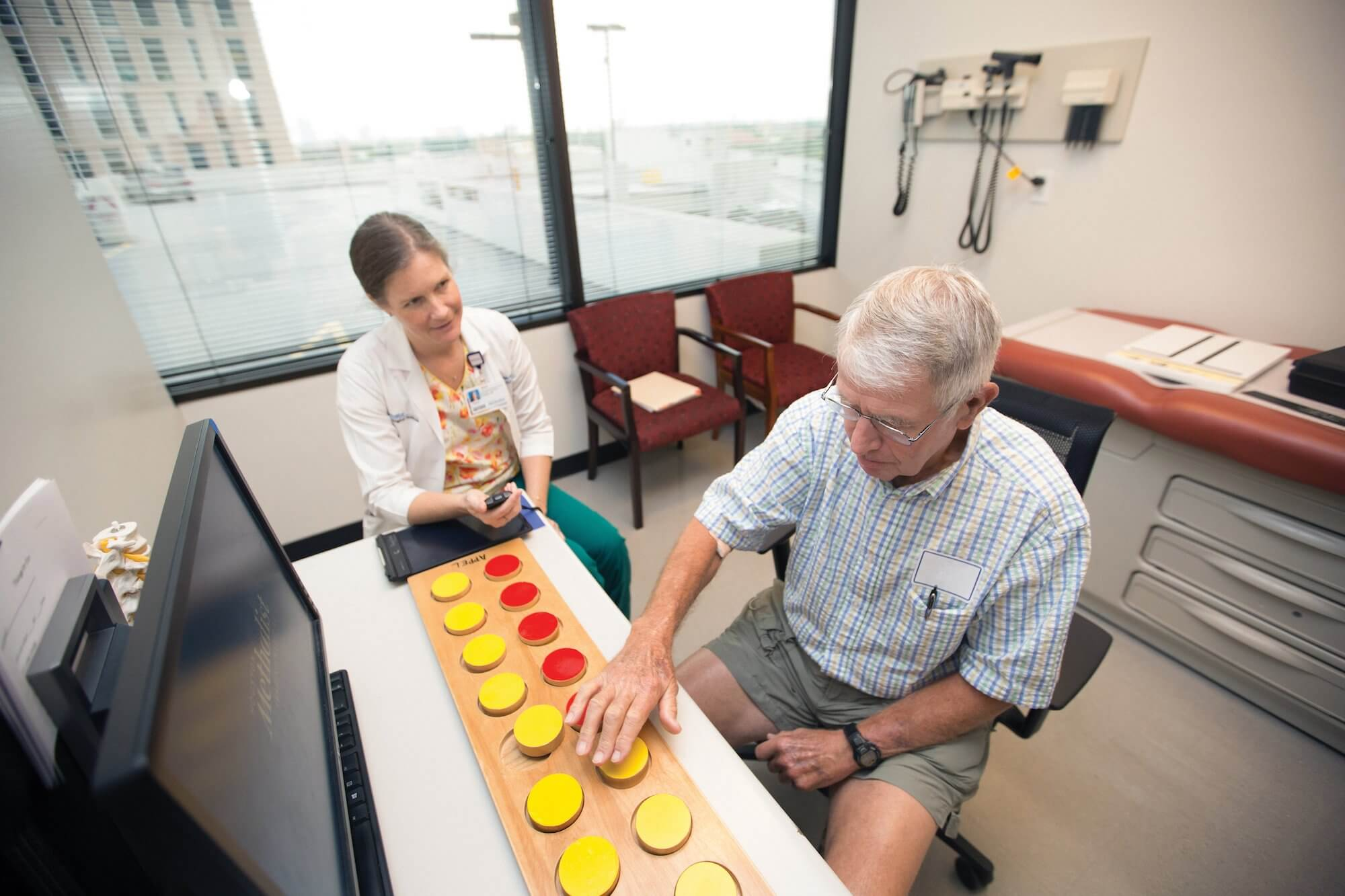 Karen Toennis, MDA/ALS Clinic coordinator, tests an ALS patient's fine motor skills using the Appel Rating Scale during a clinic session.