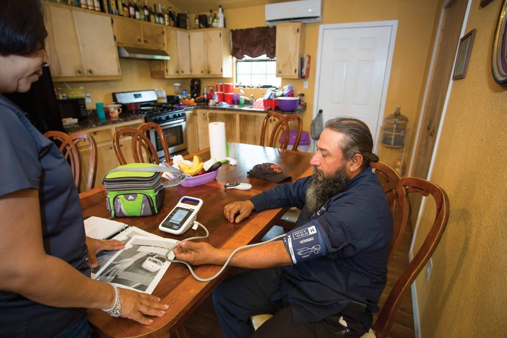 A community health worker measures Francisco Garza's blood pressure in his kitchen in San Benito, Texas.