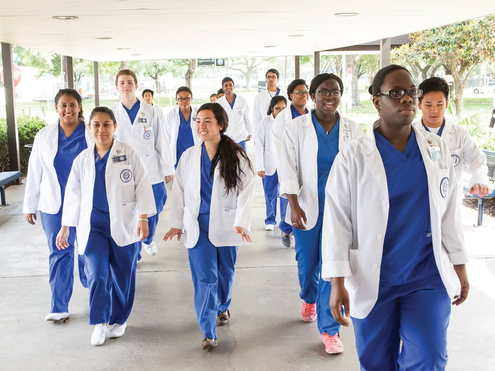 Students in scrubs return from a trip to the Texas Medical Center. During their junior and senior years, DeBakey students spend time in the medical center, shadowing medical and health science professionals.