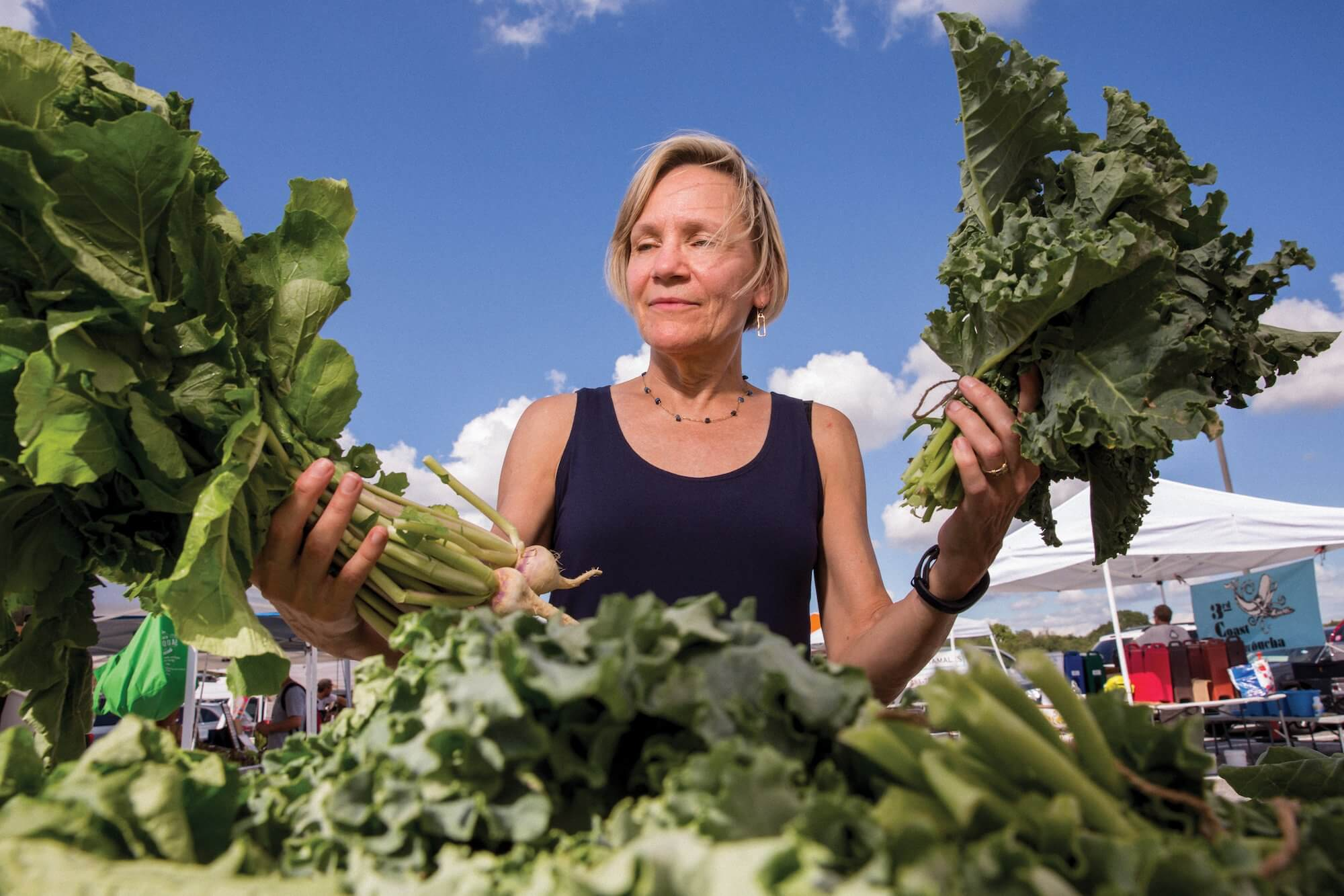 Janet Braam, Ph.D., shopping for vegetables from Atkinson Farms at the Rice University Farmers Market.