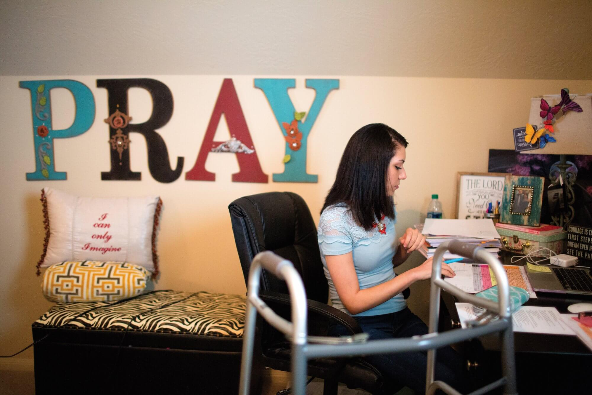Claudia Martinez studying at home in her bedroom.
