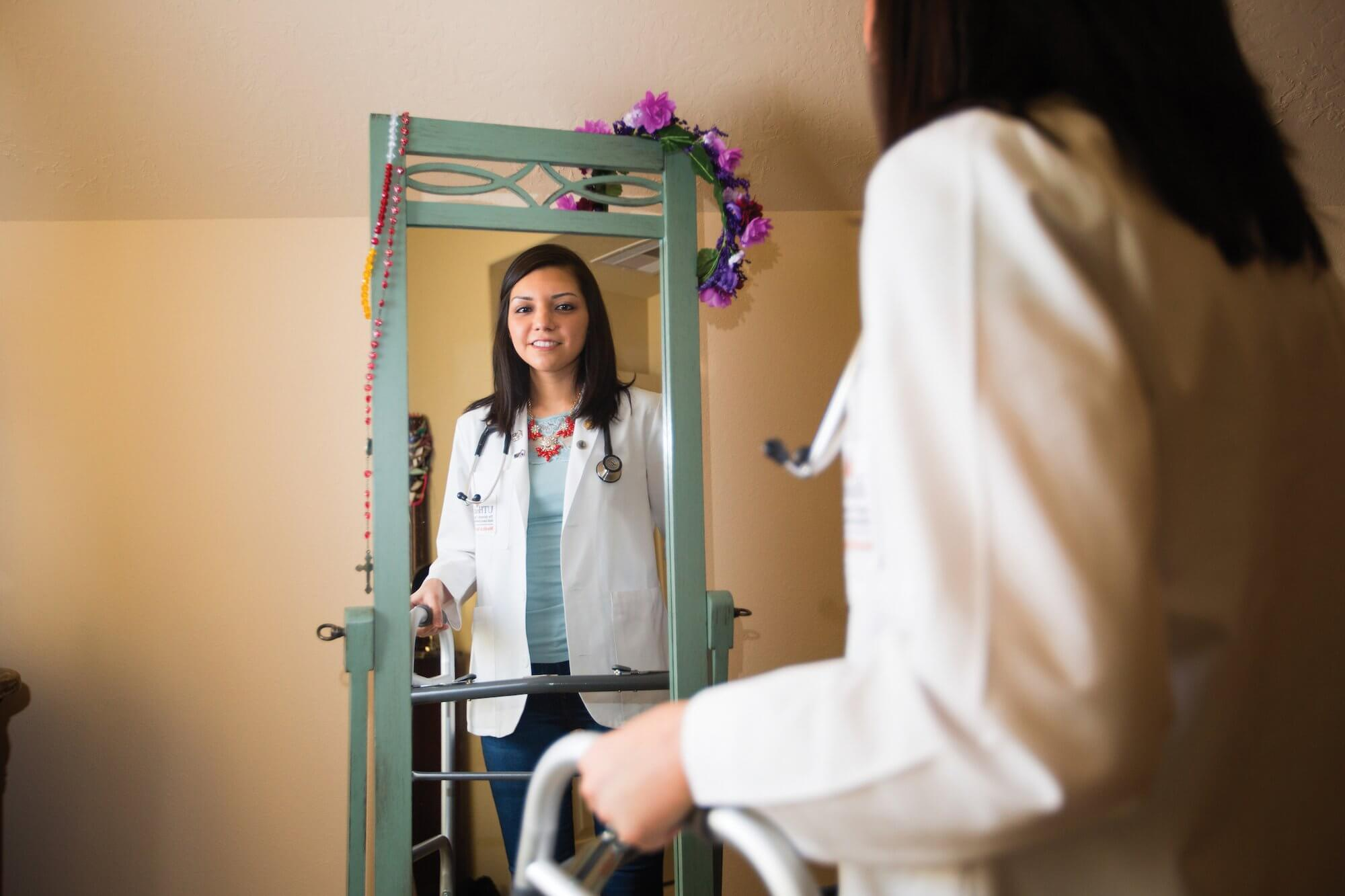 Martinez, in her white coat, takes in her reflection in a full-length mirror.