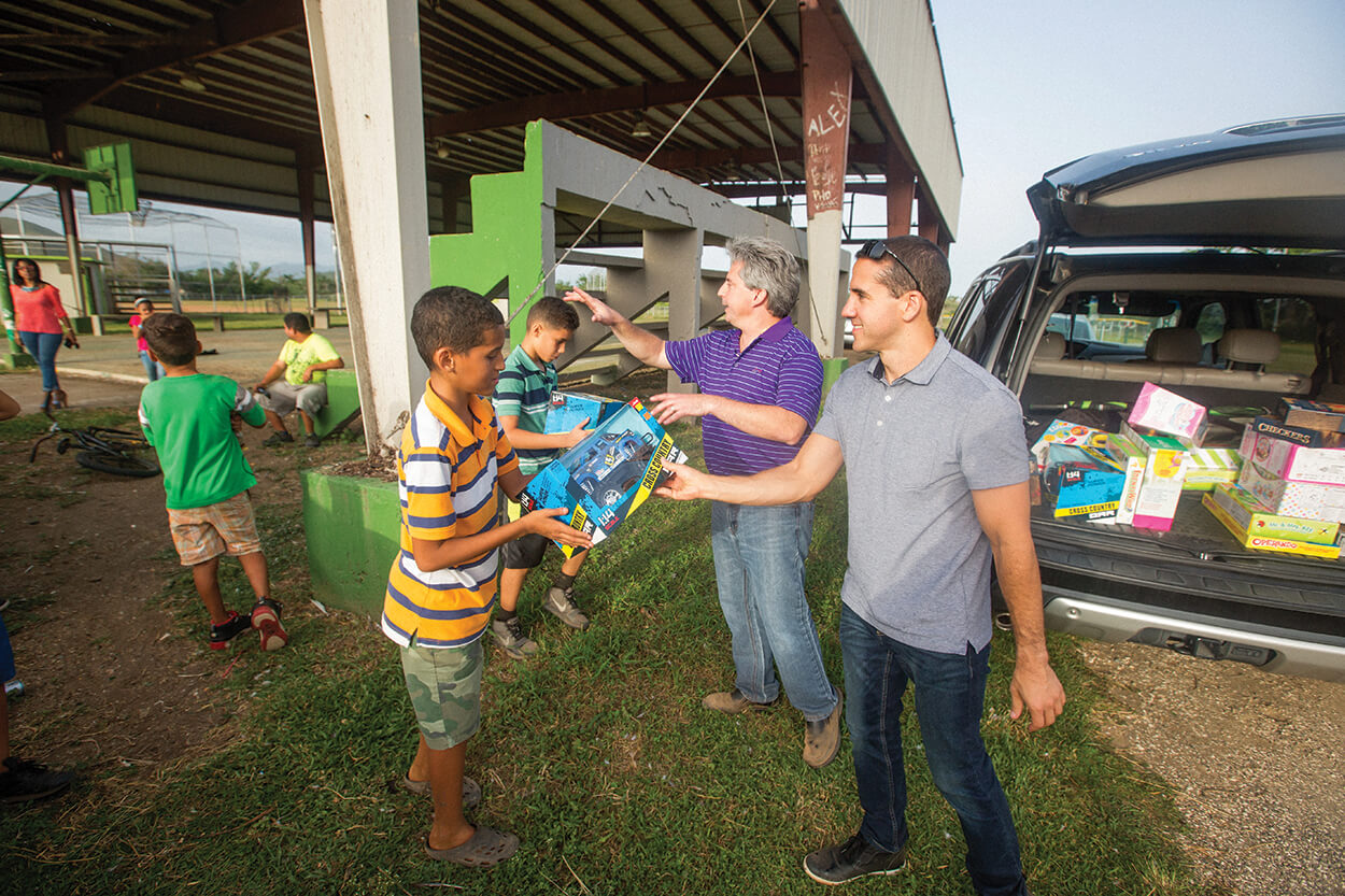 Dr. Mario Polo, left, and Dr. Ricardo Flores hand out toys to local kids in Salinas, Puerto Rico.