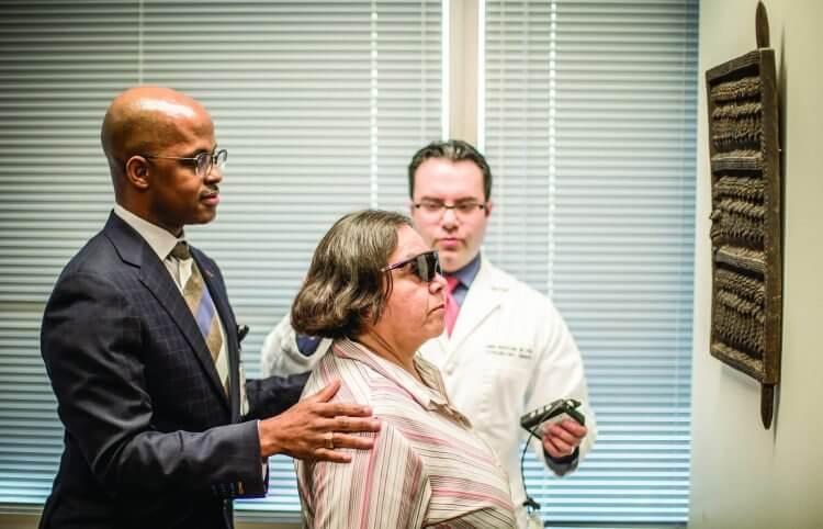 Garvin Davis, M.D., MPH, and Amir Mohsenin, M.D., Ph.D., help Lopez learn to use the Argus II bionic eye in th eRobert Cizik Eye Clinic on Feb. 12.