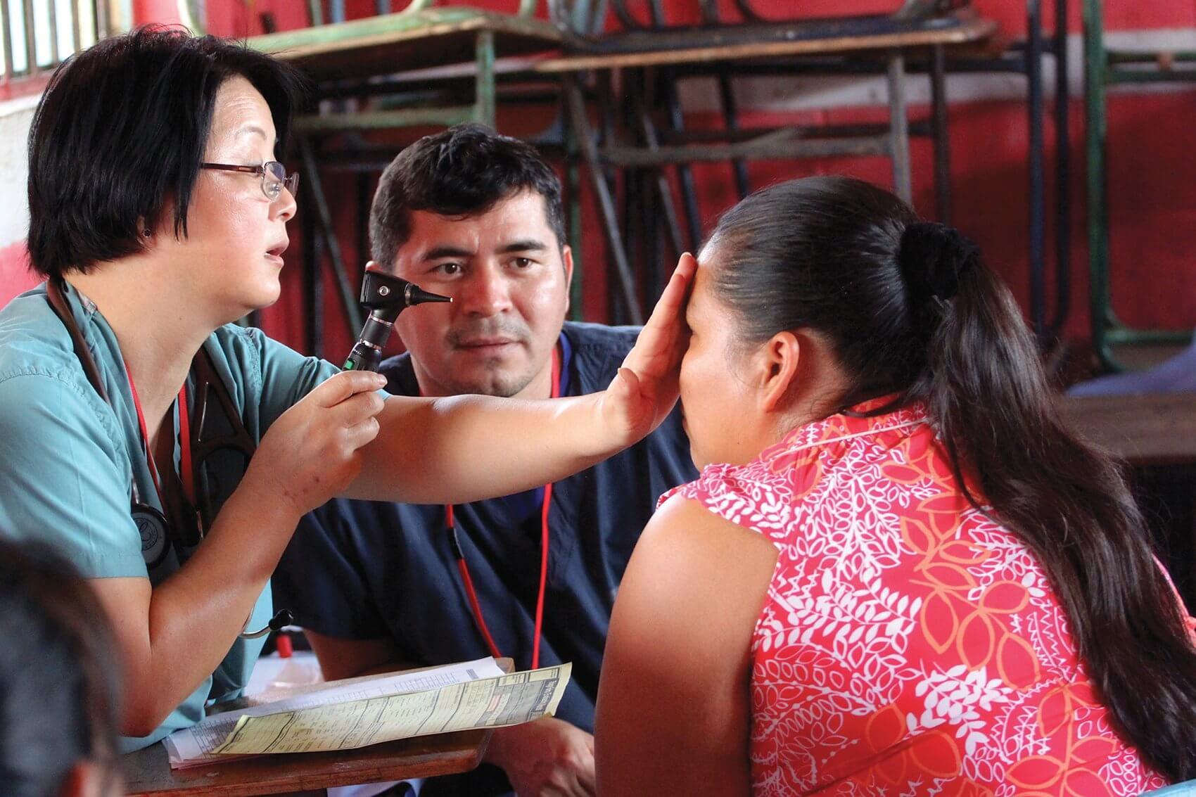 Yun Wang, M.D., examines a patient's eyes. (Credit: Josie Johnson)