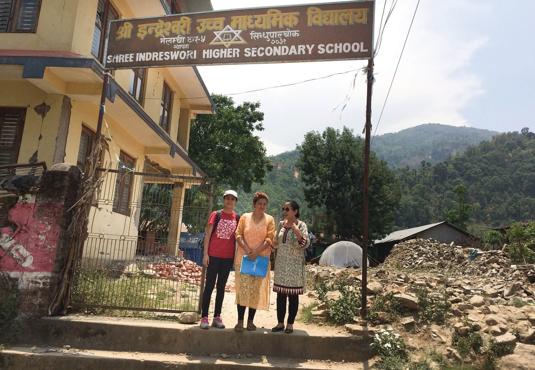 Banu stands outside one of the schools she visited to conduct a needs assessment after the earthquake.