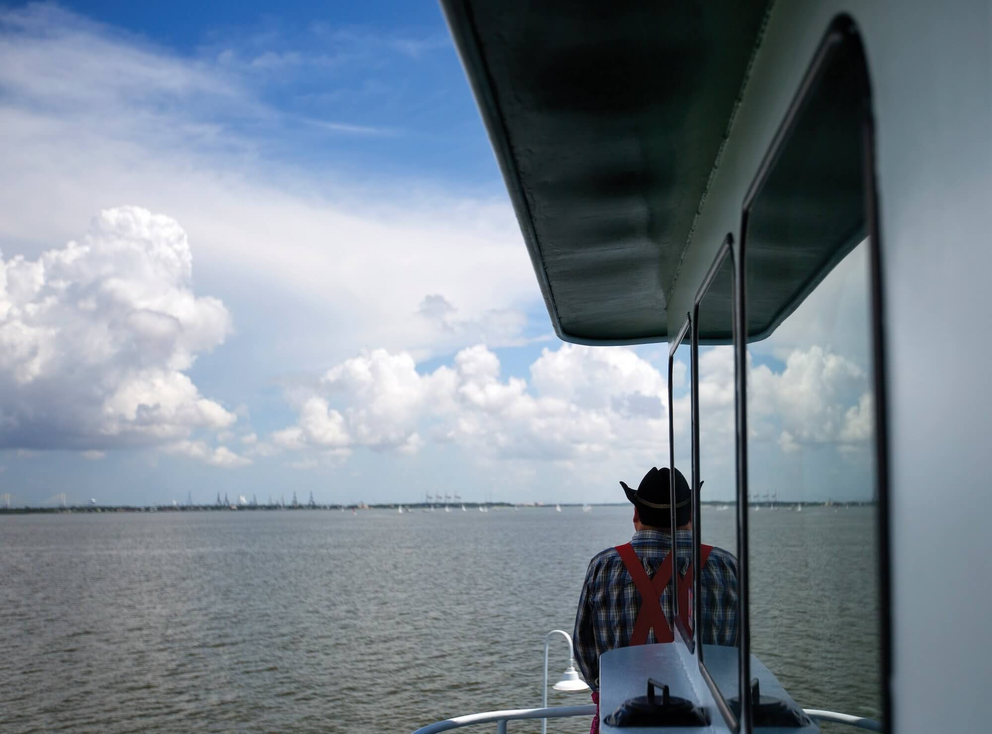 A rodeo clown looks on at the Leukemia Cup Regatta from the spectator boat.