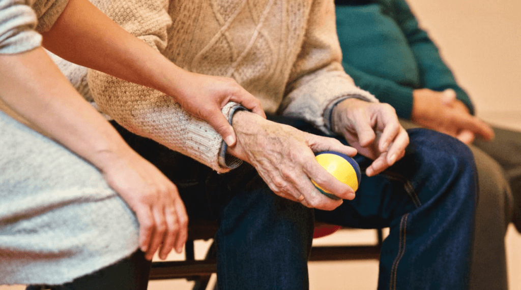 A younger person holding a senior citizen's hand as he grips a ball
