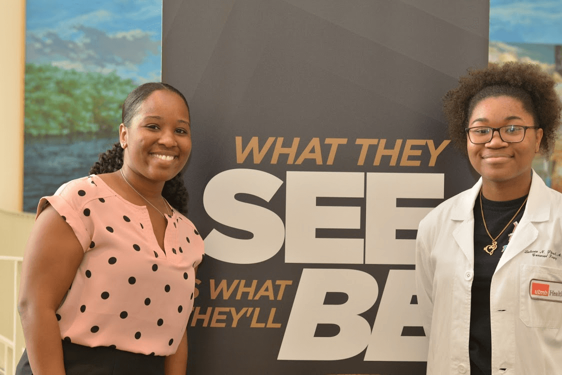 UTMB resident Laticia Stewart. M.D., left, poses with a student wearing her white coat during the 100 Black Men of Metropolitan Houston's