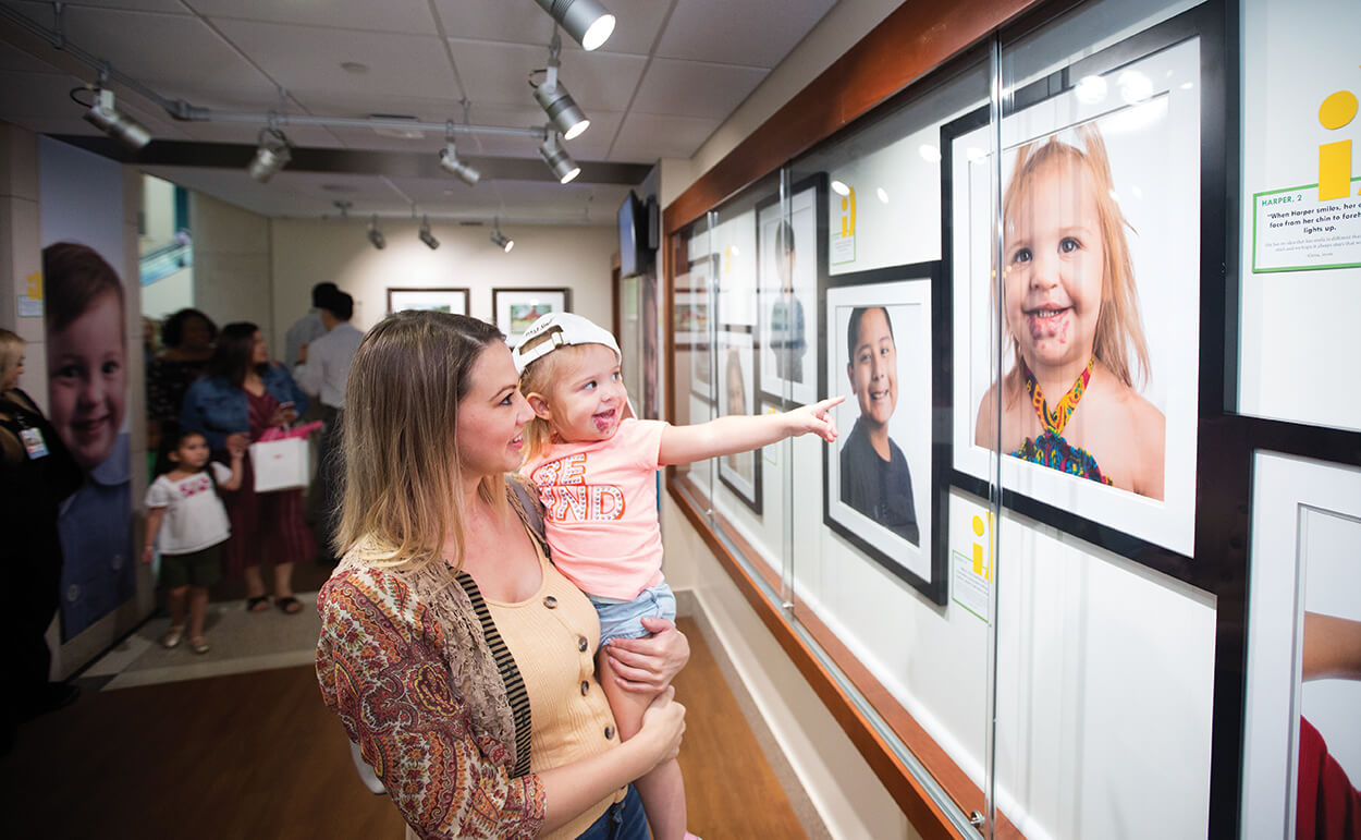 Gena Moore holds her daughter, Harper Jackson, 2, by Harper's photo in the exhibit.