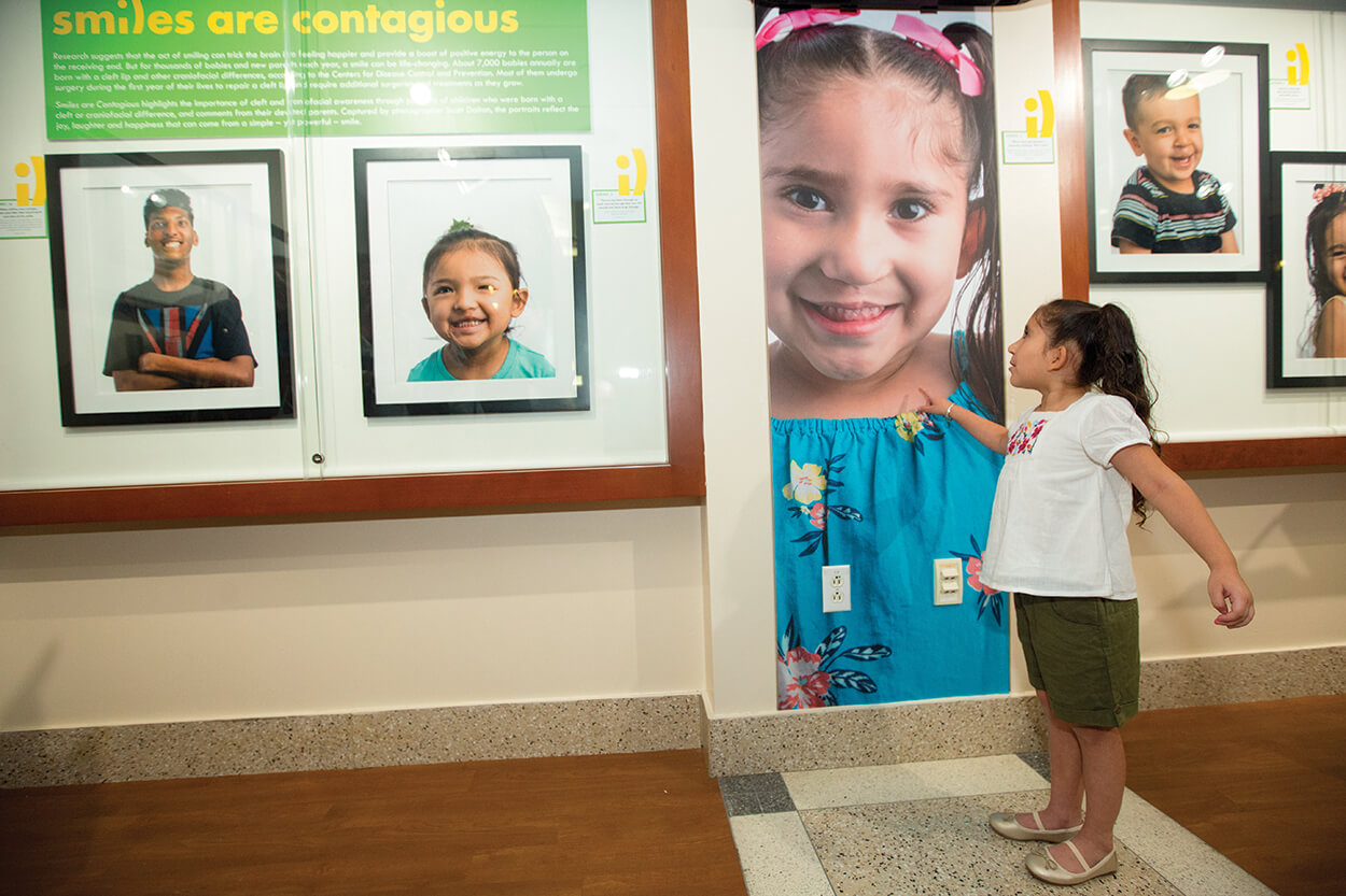 Samaya Reyes, 5, stands next to her portrait in the gallery.
