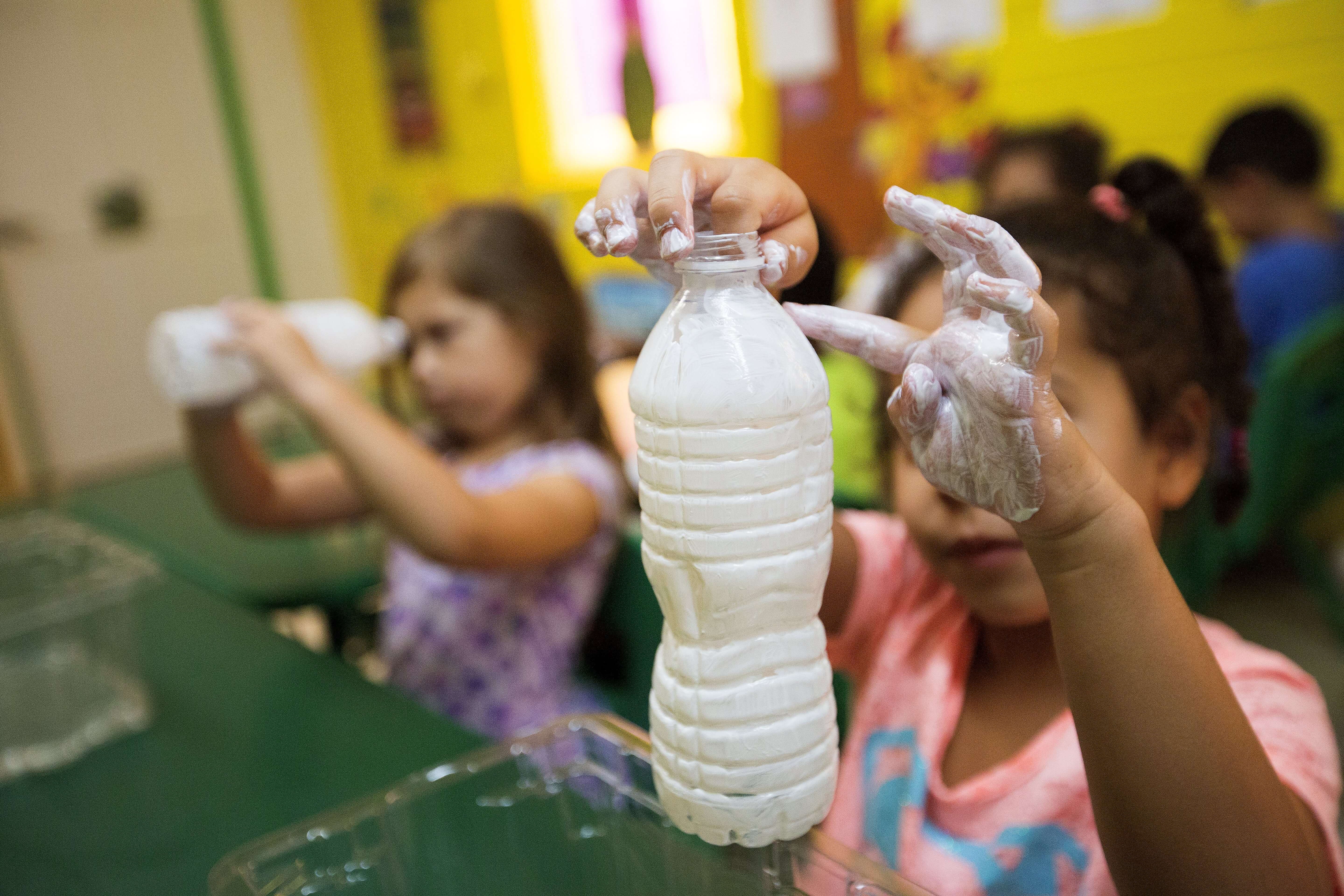 Children at MD Anderson Family YMCA cover empty water bottles with sun screen and submerge them in water to demonstrate the importance of reapplying sunscreen after swimming.