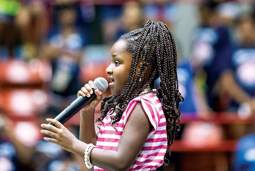 A'syria Williams gives a strong rendition of the National Anthem to commemorate the final event of the 2014 Street Olympics' Summer Games.