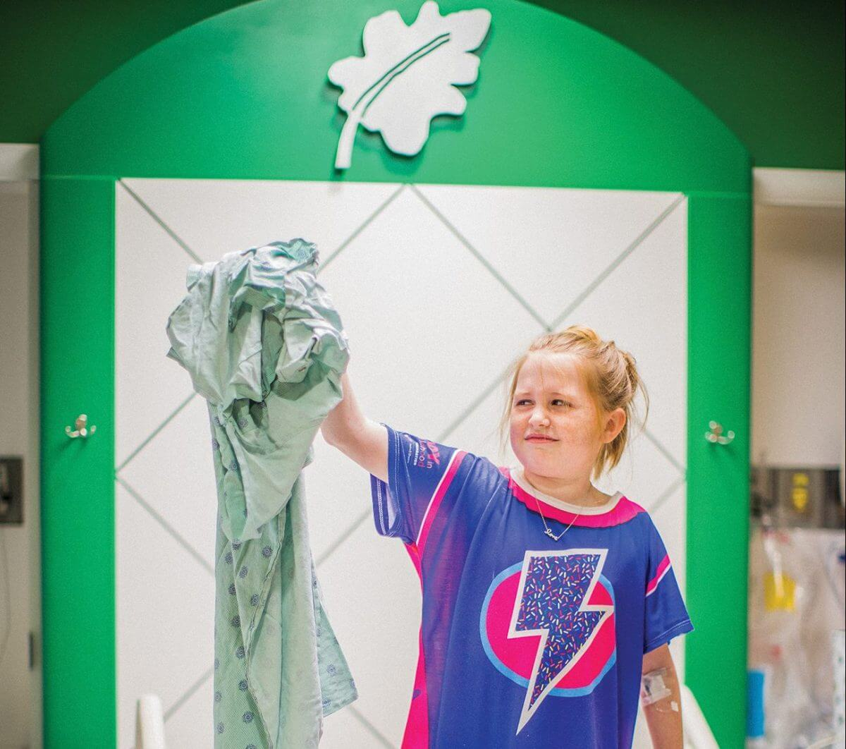 Evie Baxter, an 11-year-old patient at Children's Memorial Hermann Hospital, sports her Starlight gown while holding an old, traditional gown for comparison.