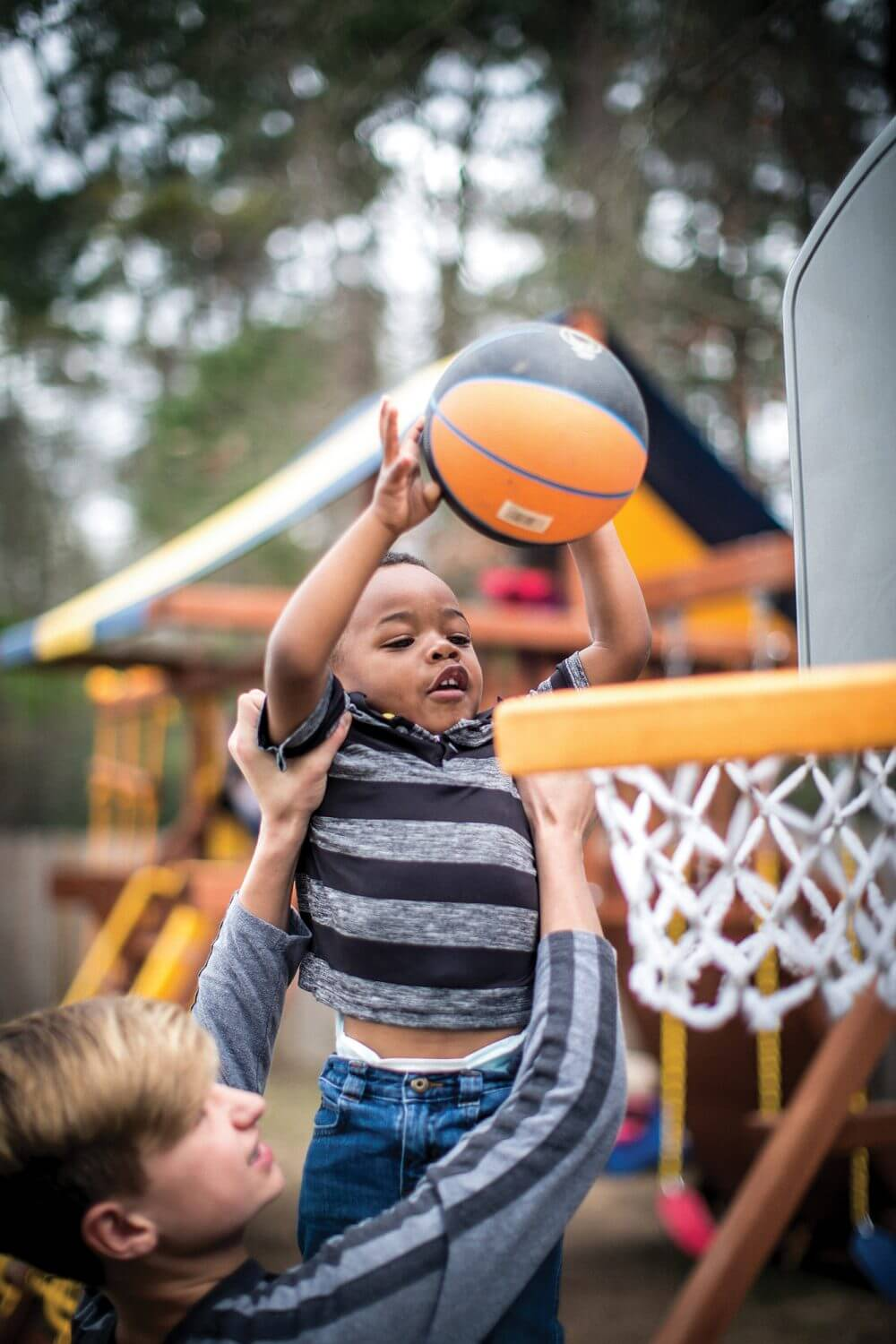 Christi Fisher's biological son, Karsen, helps his brother, Kyron, dunk a basketball. Kyron is one of four children Christi adopted through DePelchin Children's Center (Photo credit: Nick de la Torre).