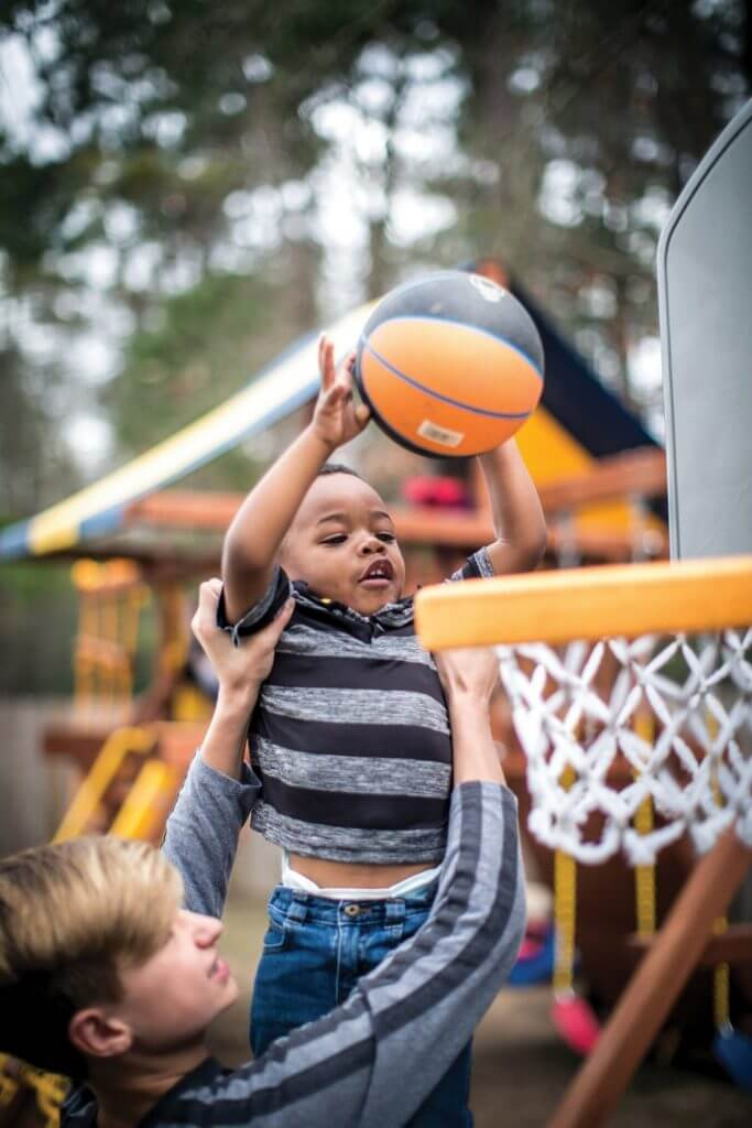Christi Fisher's biological son, Karsen, helps his brother, Kyron, dunk a basketball. Kyron is one of four children Christi adopted through DePelchin Children's Center.