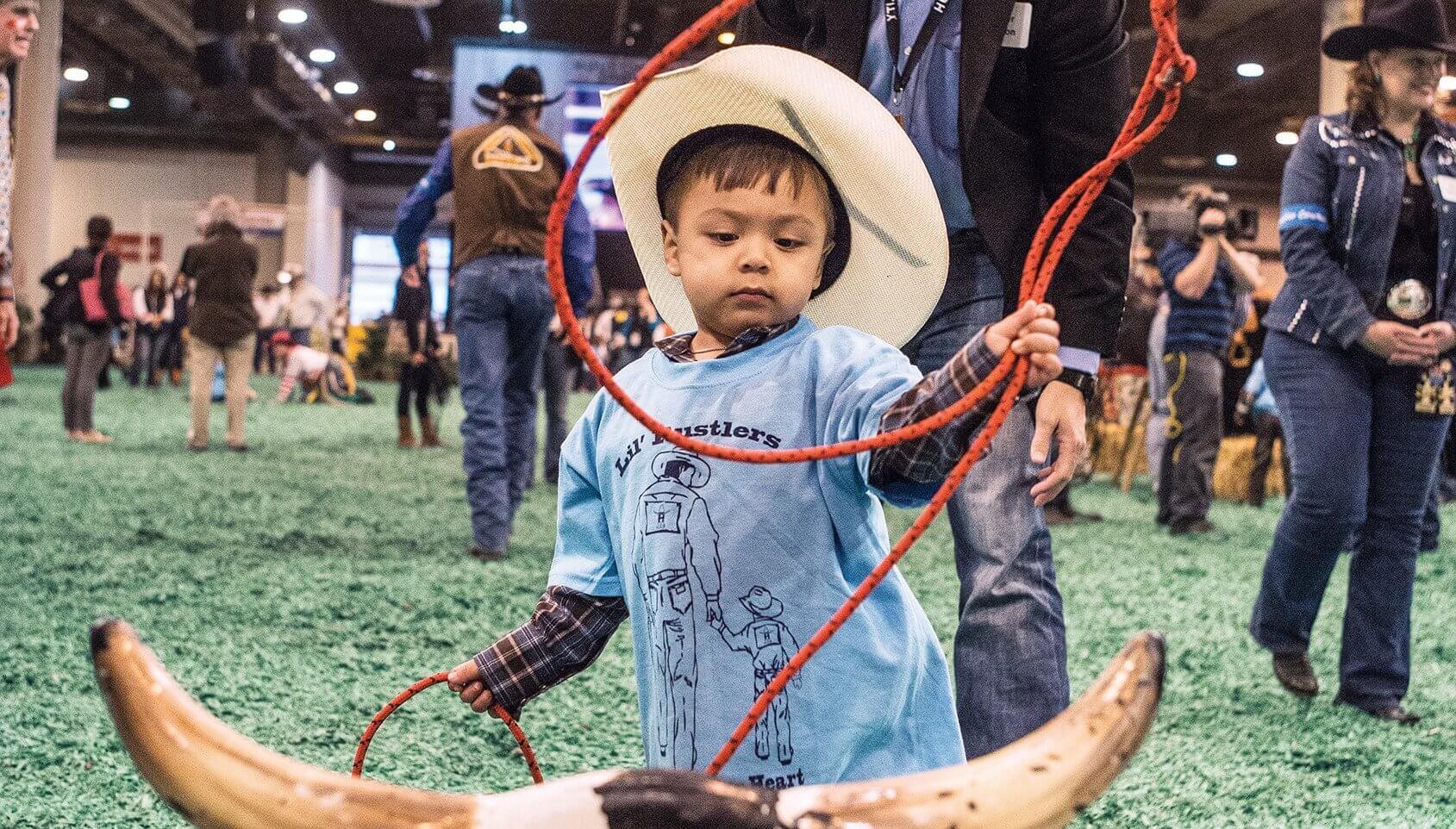 Three-year-old Caleb ropes a steer under the watchful eye of his volunteer cowboy.