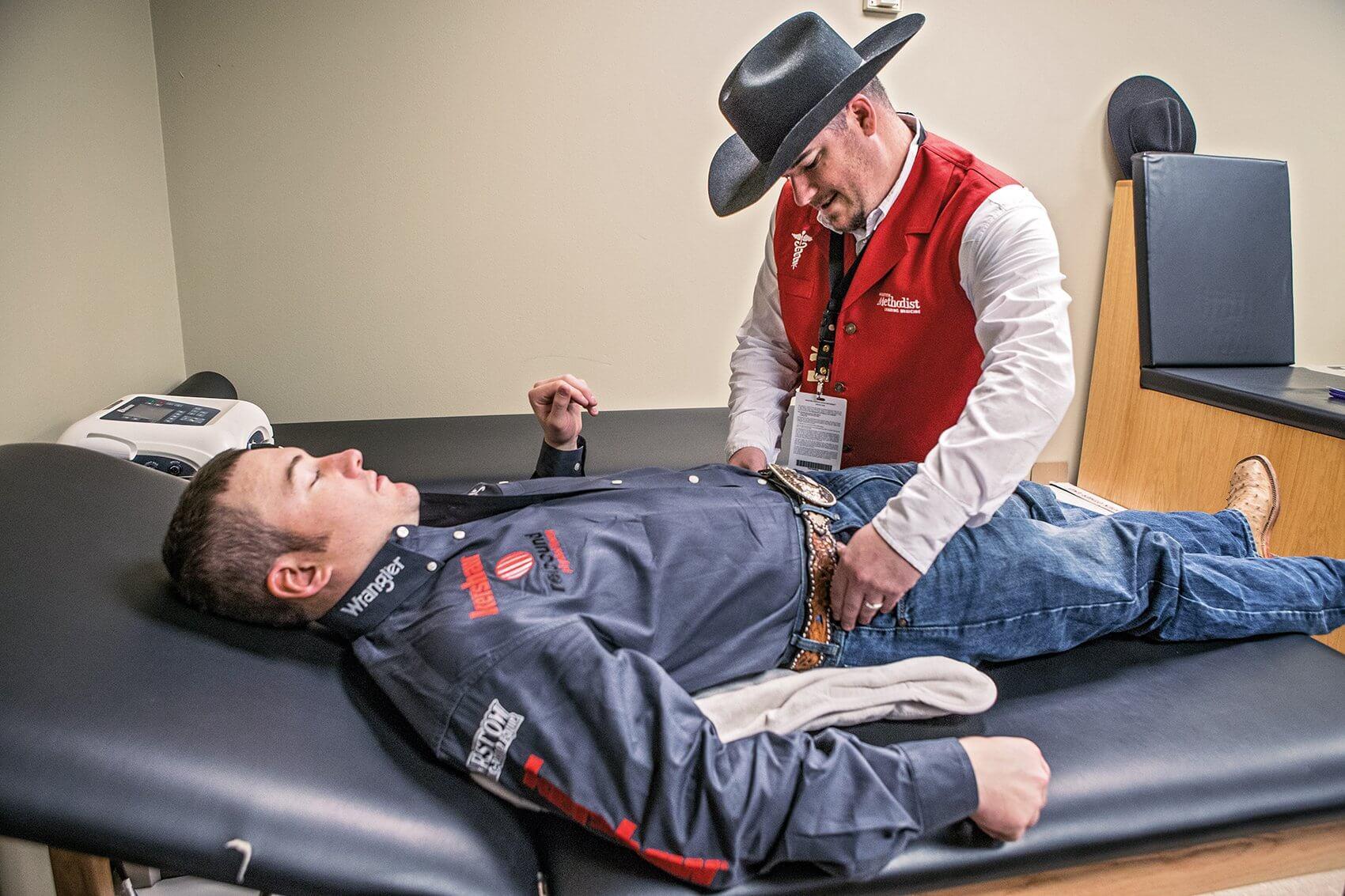 Bareback rider Steven Peebles, left, is examined by Houston Methodist Athletic Trainer Jeff Collins.