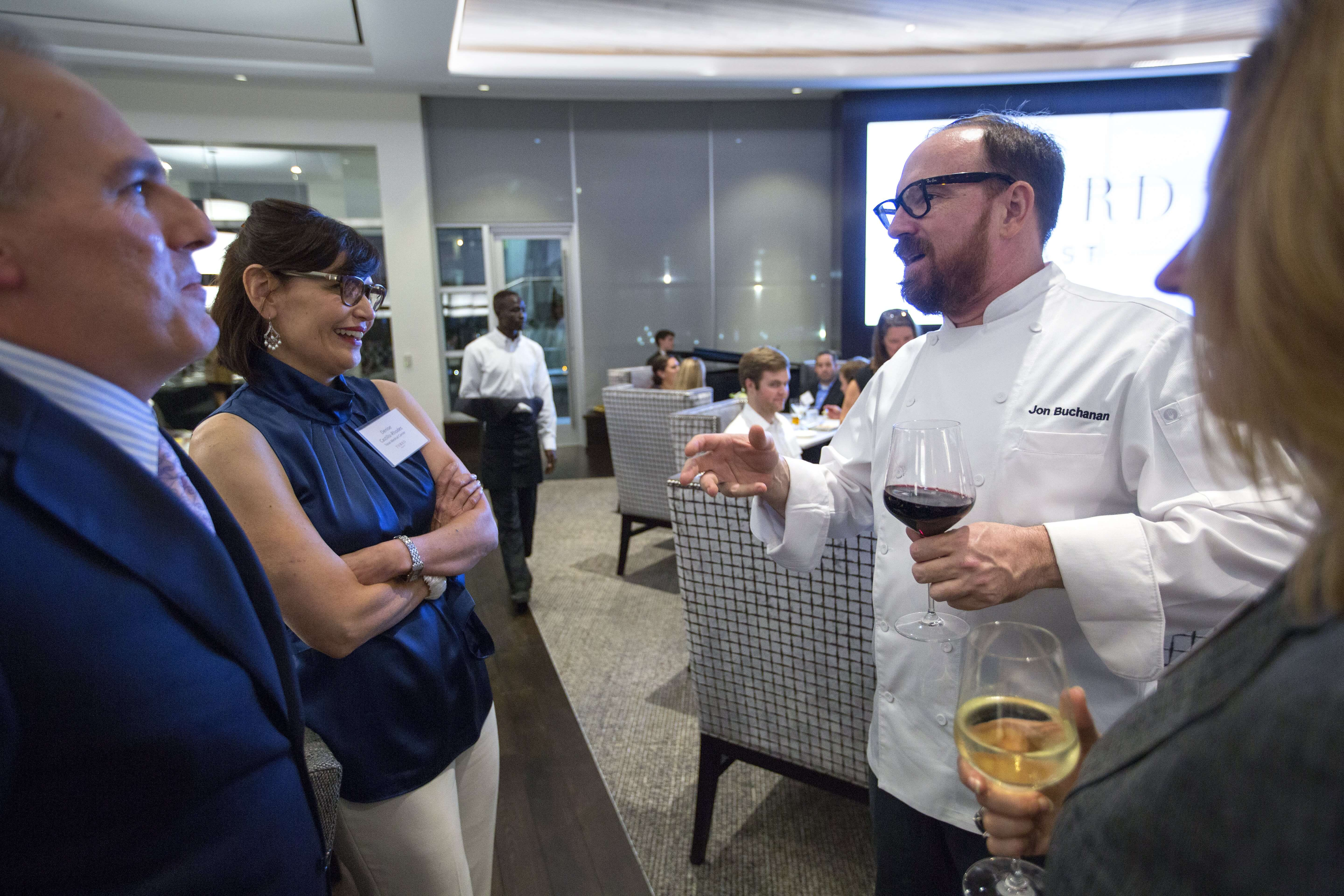 Executive chef Jon Buchanan speaks with Texas Medical Center chief financial officer at the grand opening of Third Coast.