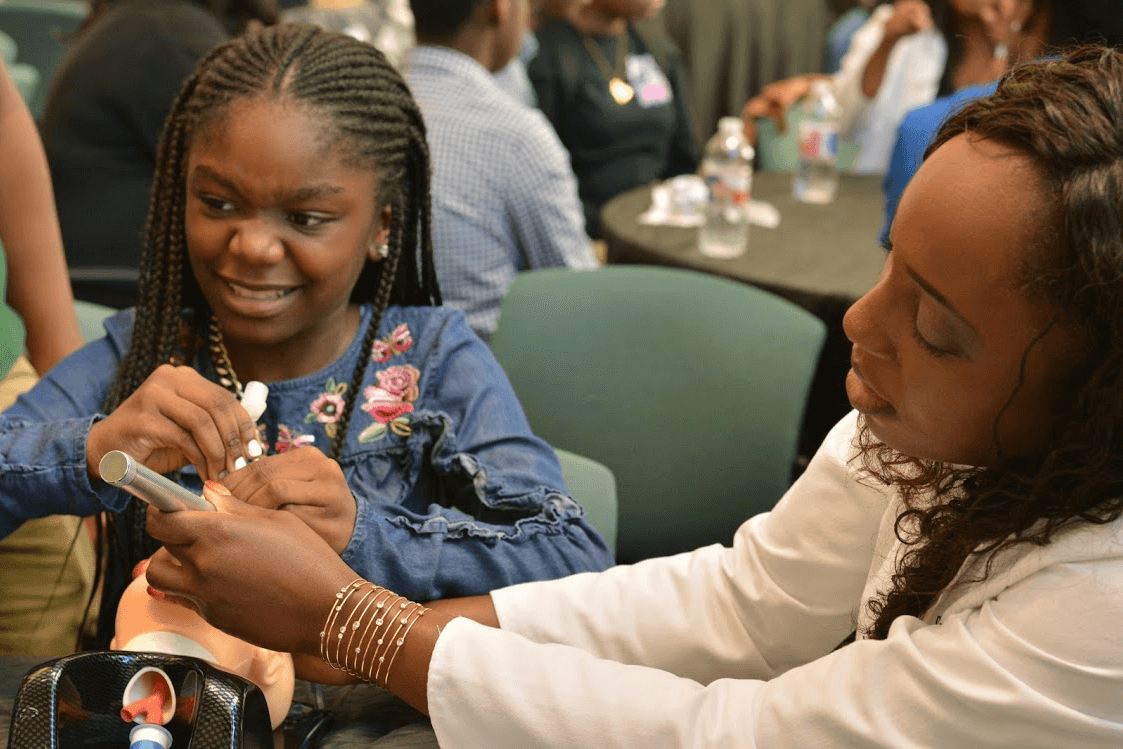 MD Anderson anesthesiologist Ifeyinwa Ifeanyi-Pillette, M.D., helps a student with a medical demonstration during the 100 Black Men of Metropolitan Houston's
