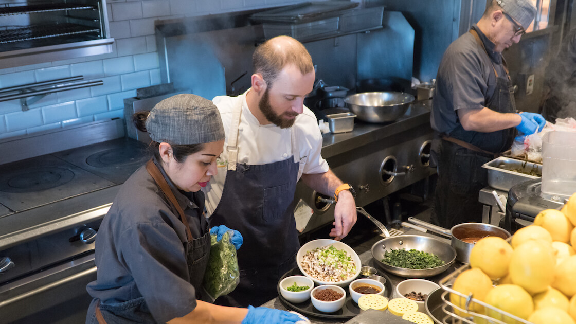 True Food Kitchen's executive sous chef Robert Luttrell, center, prepares ingredients for lettuce cups, which he will demonstrate for a video.