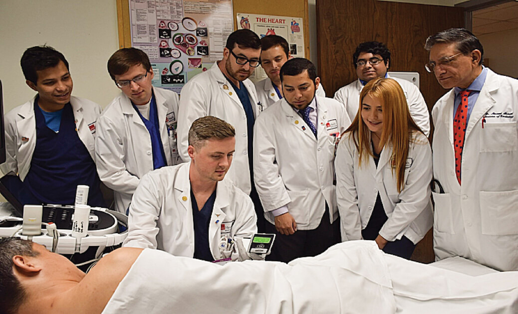 Masood Ahmad, M.D., far right, professor of internal medicine and director of UTMB's Cardiac Echocardiography Lab, supervises students using a handheld ultrasound on a patient.