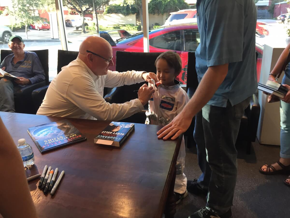 Scott Kelly signs Eliot Rambow's space suit at his book signing at Brazos Bookstore on Sunday, Oct. 27, 2018.