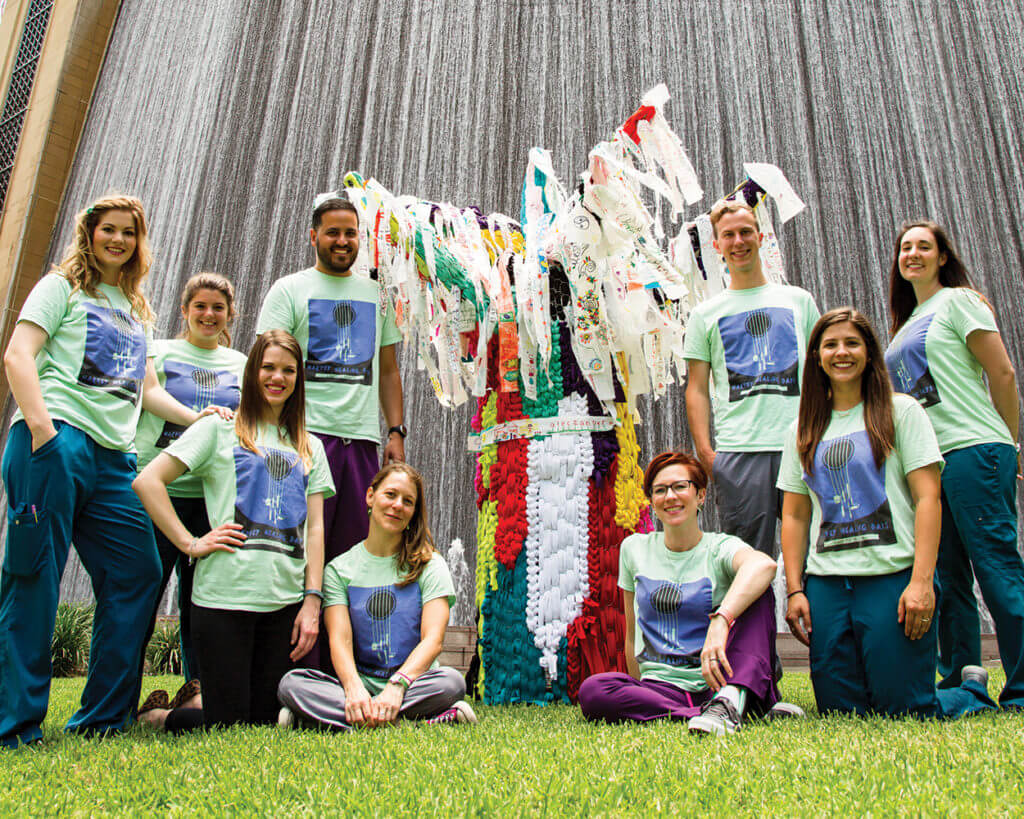 Creative arts therapists from TEXAS CHILDREN'S HOSPITAL, HOUSTON METHODIST HOSPITAL and CHILDREN'S MEMORIAL HERMANN HOSPITAL posed with the Harvey Healing Tree, part of the Harvey Arts Recovery Project. The therapists held four Harvey Healing Days around the city to help repair emotional wounds left by Hurricane Harvey, during which guests had a chance to express themselves on canvas strips that have now been integrated into one collective piece of art (Credit: William Duncan Beard).