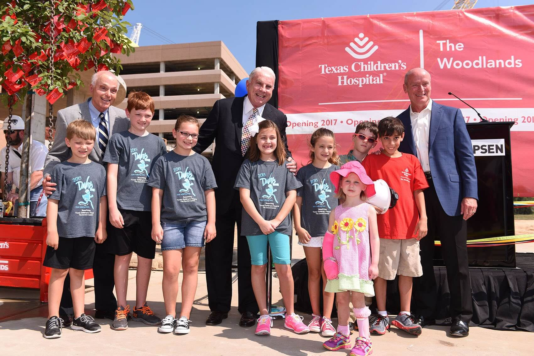(L to R): Howard Tellepsen, president of Tellepsen Builders; Mark A. Wallace, president and CEO of Texas Children's Hospital; and Dr. Mark W. Kline, physician-in-chief at Texas Children's Hospital, smile with patients from the north Houston area and students from David Elementary School before the ceremony. (Credit: Paul Vincent Kuntz/Texas Children's Hospital)