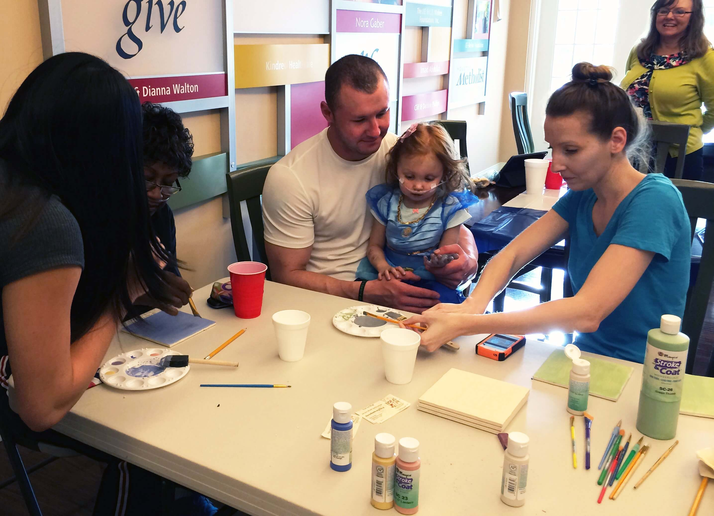 The Rainey family decorates a tile during Family Fun Night. Aubrey, 3, is waiting for a liver transplant.