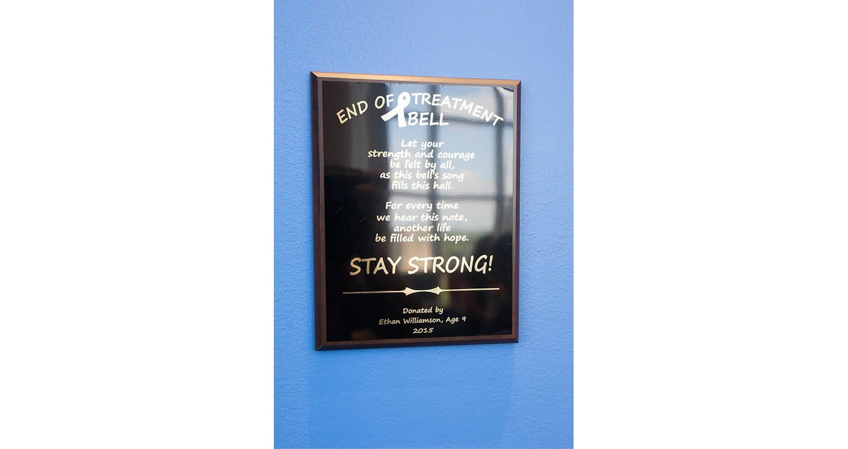 The plaque that hangs next to the end of treatment bell. (Credit: John R. Lewis Photography)