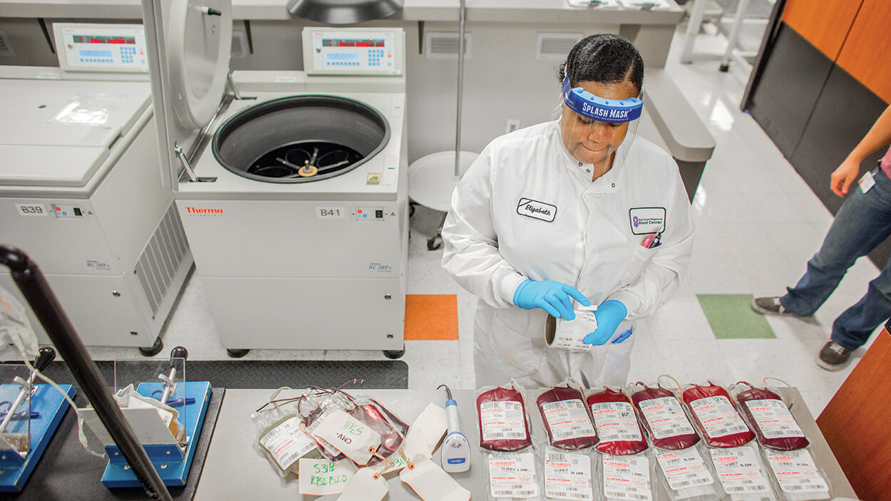Component lab technician Elizabeth Scott prepares blood products for a spin in the centrifuge at Gulf Coast Regional Blood Center.
