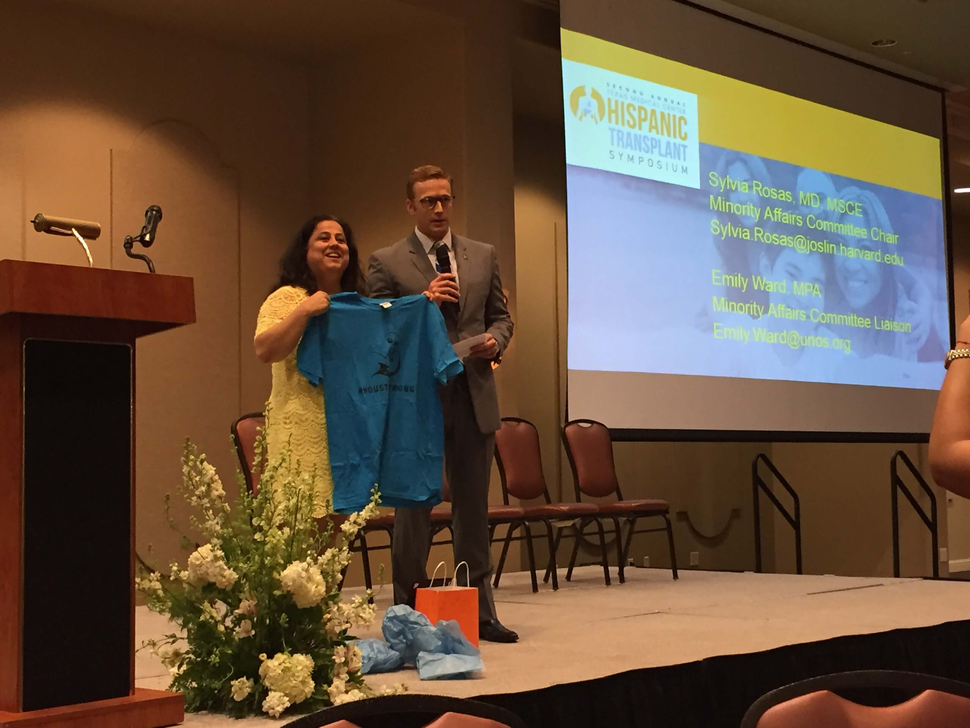 Dr. Mark Hobeika presents keynote speaker Dr. Sylvia Rosas with a Houston Strong t-shirt after her presentation.