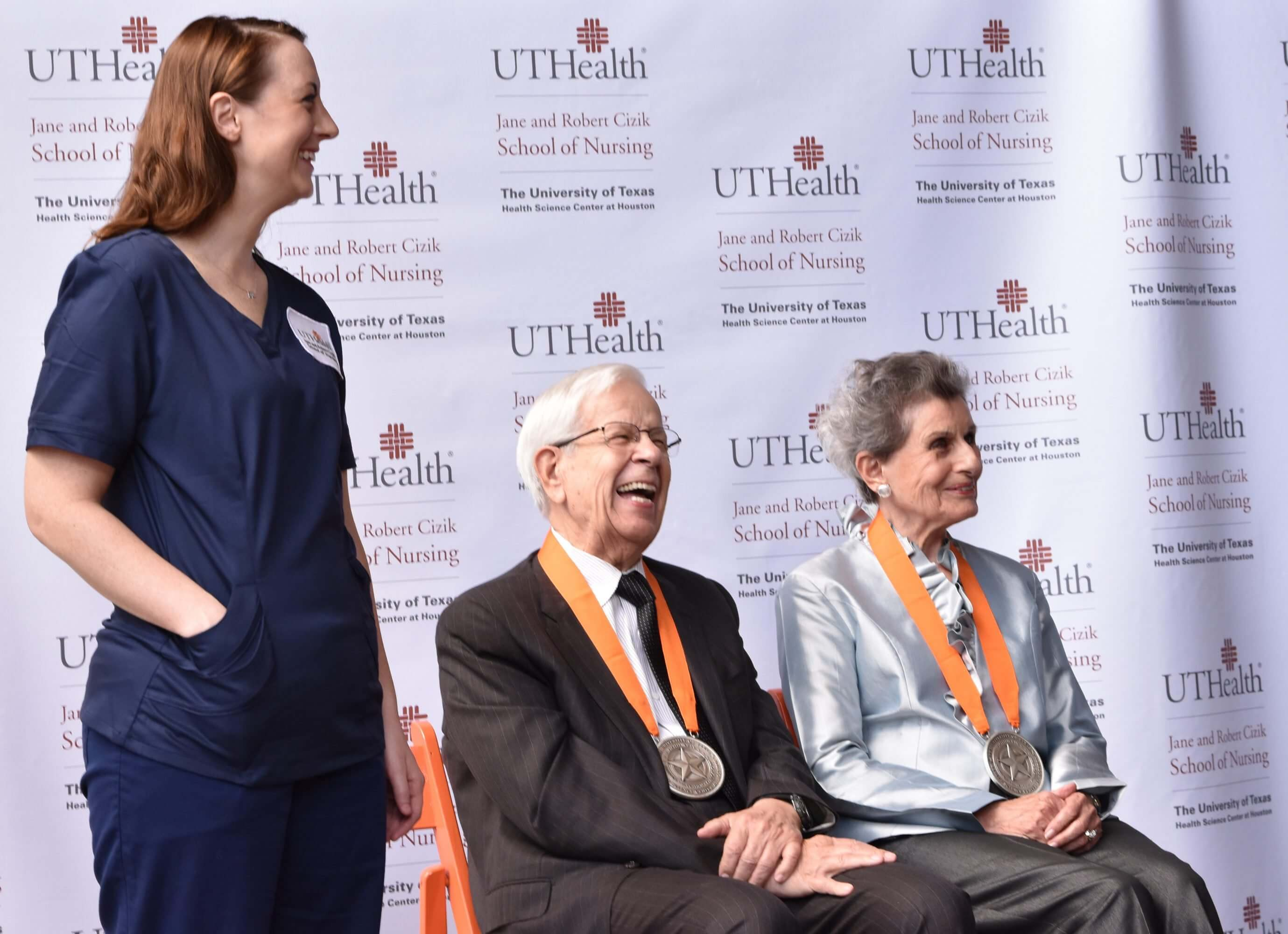 Cizik School of Nursing student Krista Robinson joins Robert and Jane Cizik on stage to show the school's new patch on her uniform. Photo by Katy Umana/UTHealth.