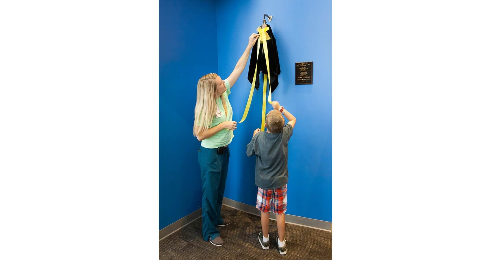 Ethan Williamson and Nicolle Eighmy, child life specialist at Texas Children's Cancer and Hematology Centers, unveil the end of treatment bell. (Credit: John R. Lewis Photography)
