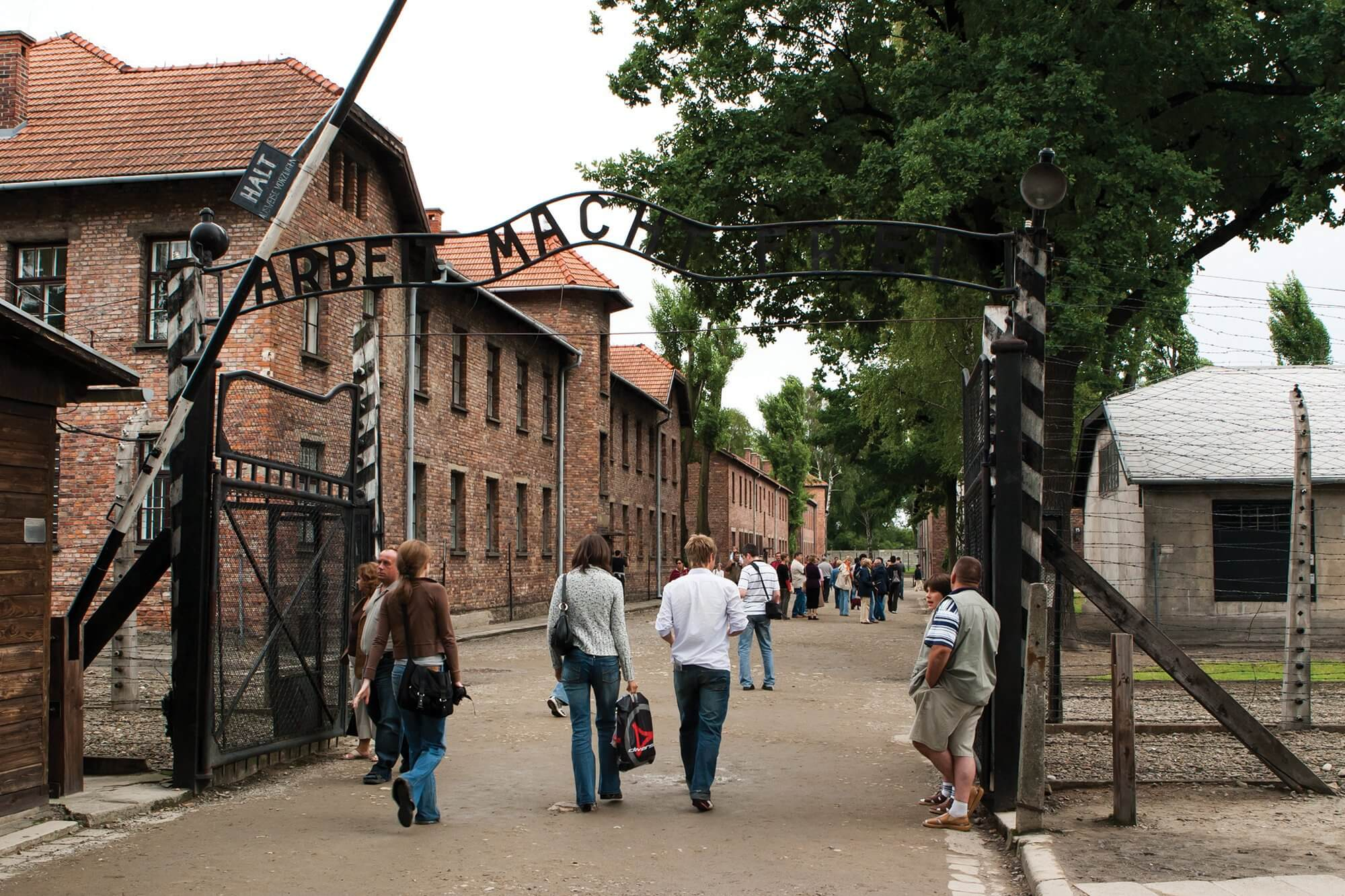 Tourists walk through the main entrance to Auschwitz concentration camp. Today, the camp functions as a museum. Credit: Martin Dimitrov/ iStock