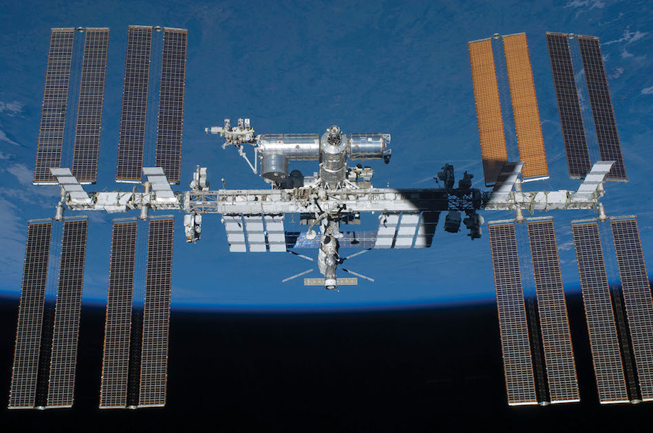 The International Space Station appears against the Earth's horizon.