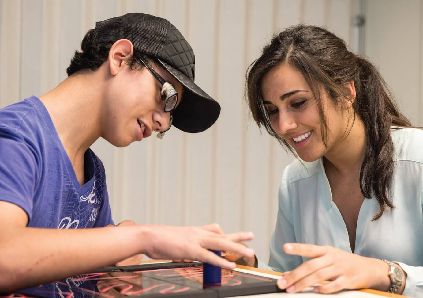 Sonia Garcia, a senior at Rice University, guides Brandon Sierra, a patient at Shriners Hospital for Children, Houston, through tasks intended to measure his dex- terity. (Credit: Jeff Fitlow/Rice University)