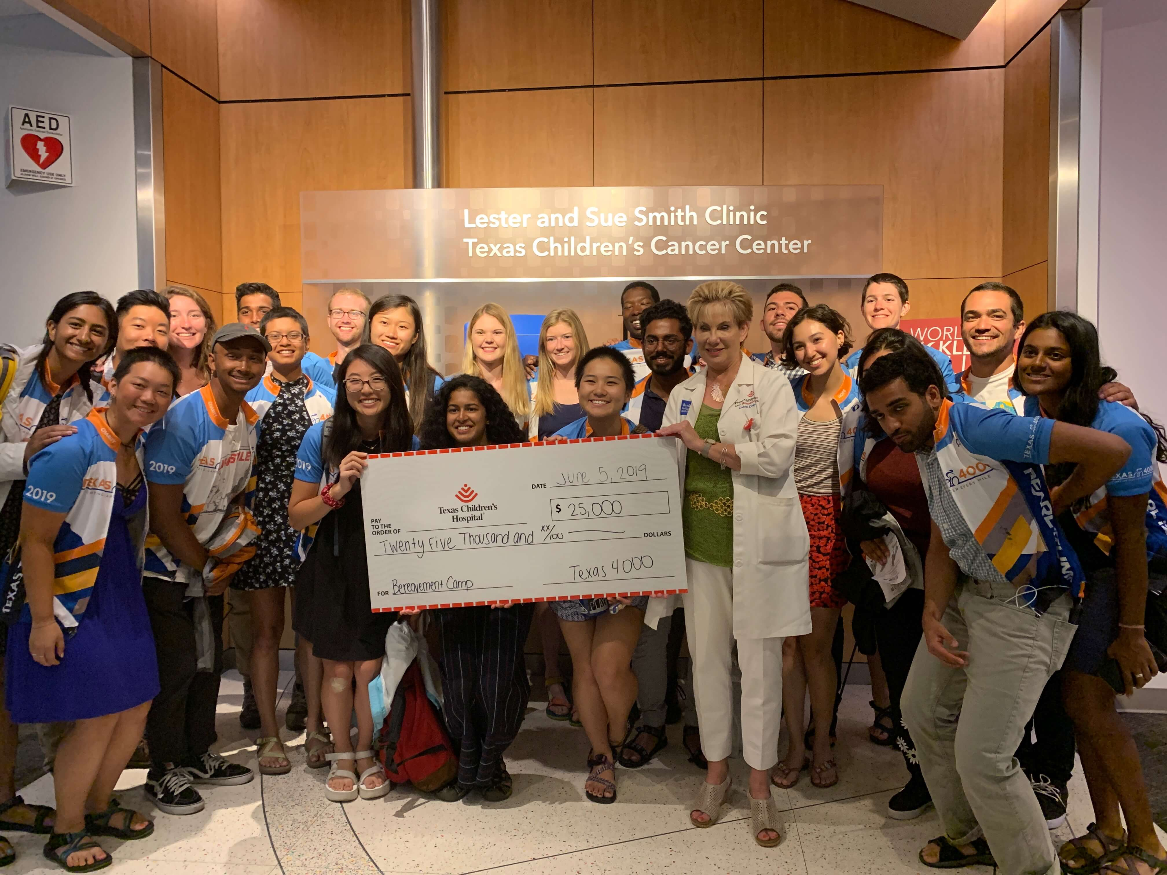 Texas 4000 riders present a $25,000 check to ZoAnn Dreyer, M.D., at Texas Children's to offer bereavement retreats for Spanish-speaking families on June 5, 2019.
