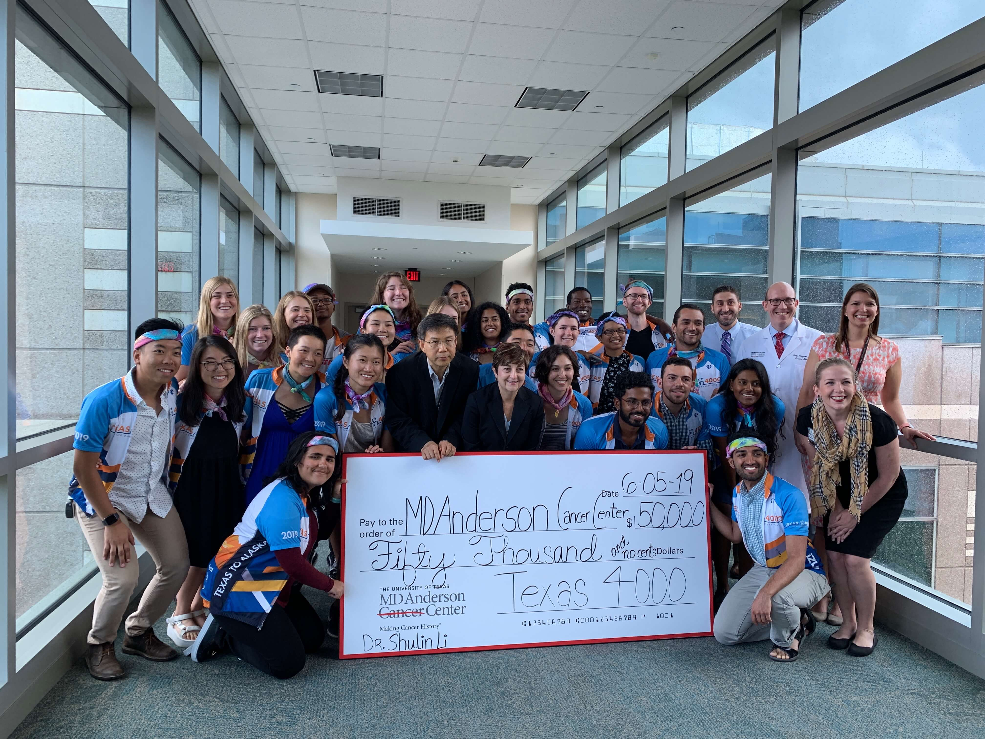 Texas 4000 riders present a $50,000 check to Shulin Li, Ph.D., to continue his research in circulating tumor cells on June 5, 2019.