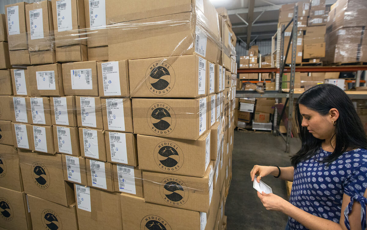 Heidi Alvarez, director of operations for Medical Bridges, prepares supplies for shipment to the Bahamas.