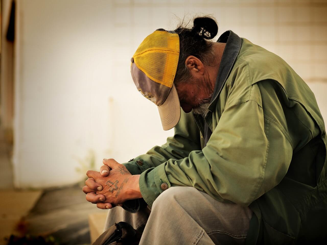 A homeless man sits on a roadside.