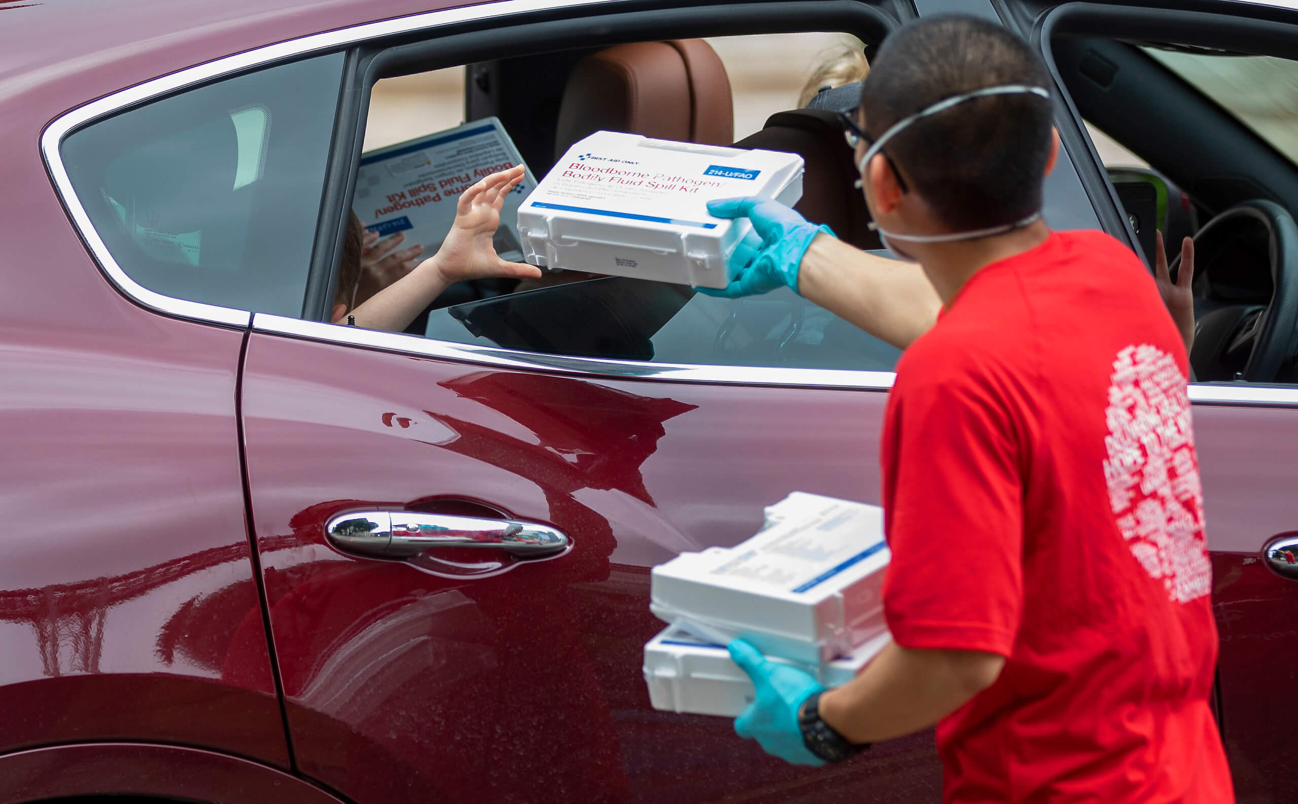 Project C.U.R.E. volunteer Ray Wang accepts a body fluid spill kit from a resident during a PPE donation drive on Wednesday, April 8, 2020, in Houston.