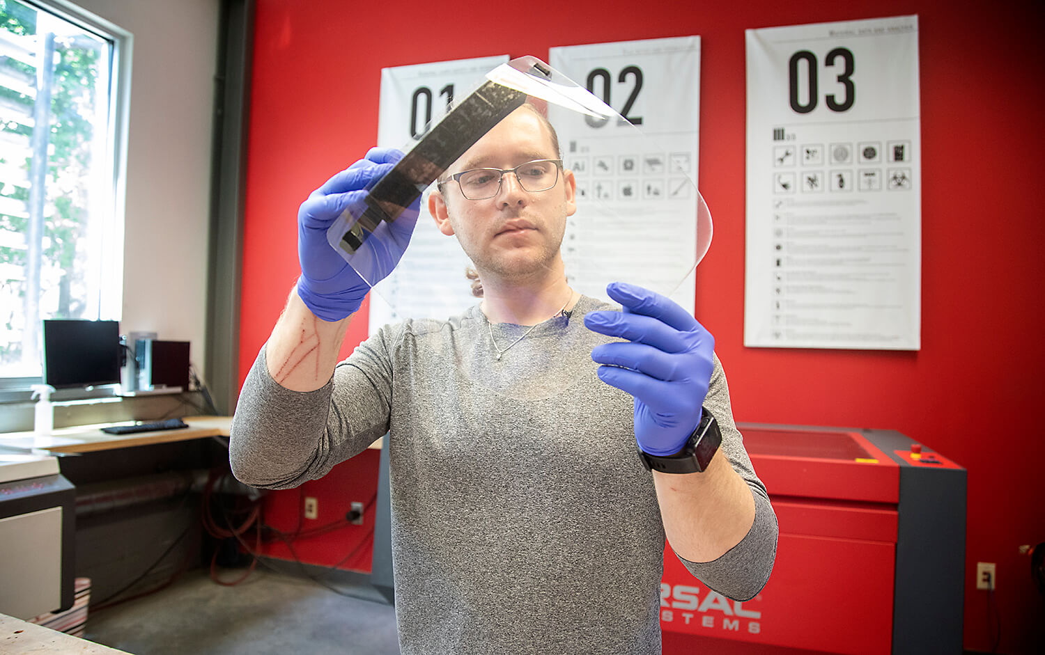 Aaron McEuen, the instructional lab manager of the University of Houston's Burdette Keeland Jr. Design Exploration Lab, examines one of the face shields his lab manufactured for Harris Health System.